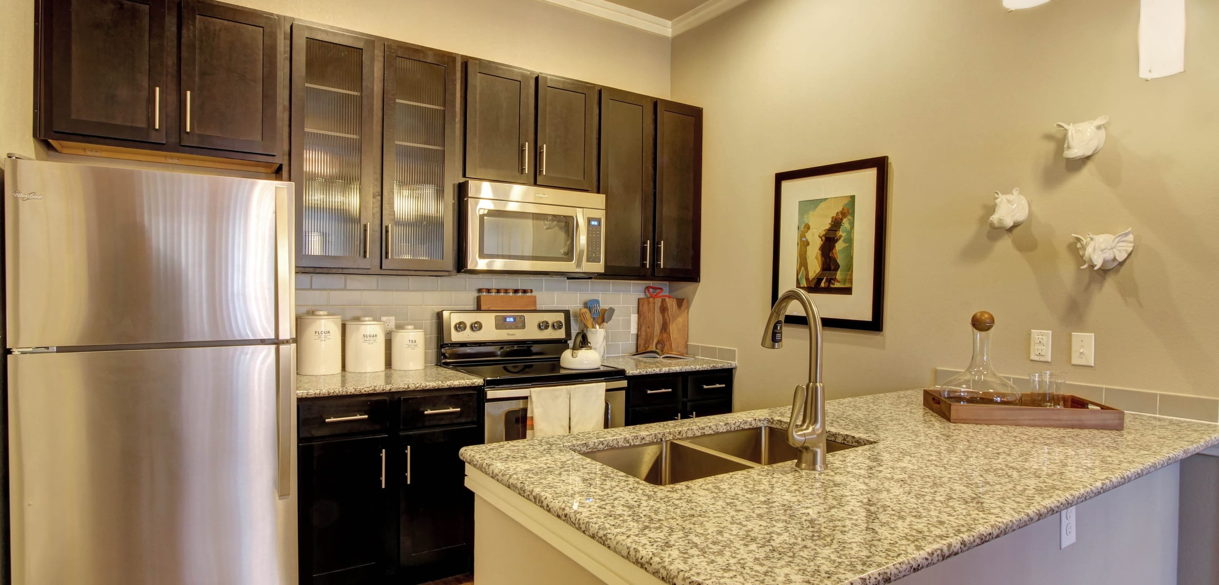 Modern kitchen with stainless steel appliances and granite countertops at Marquis at Barton Trails in Austin, Texas