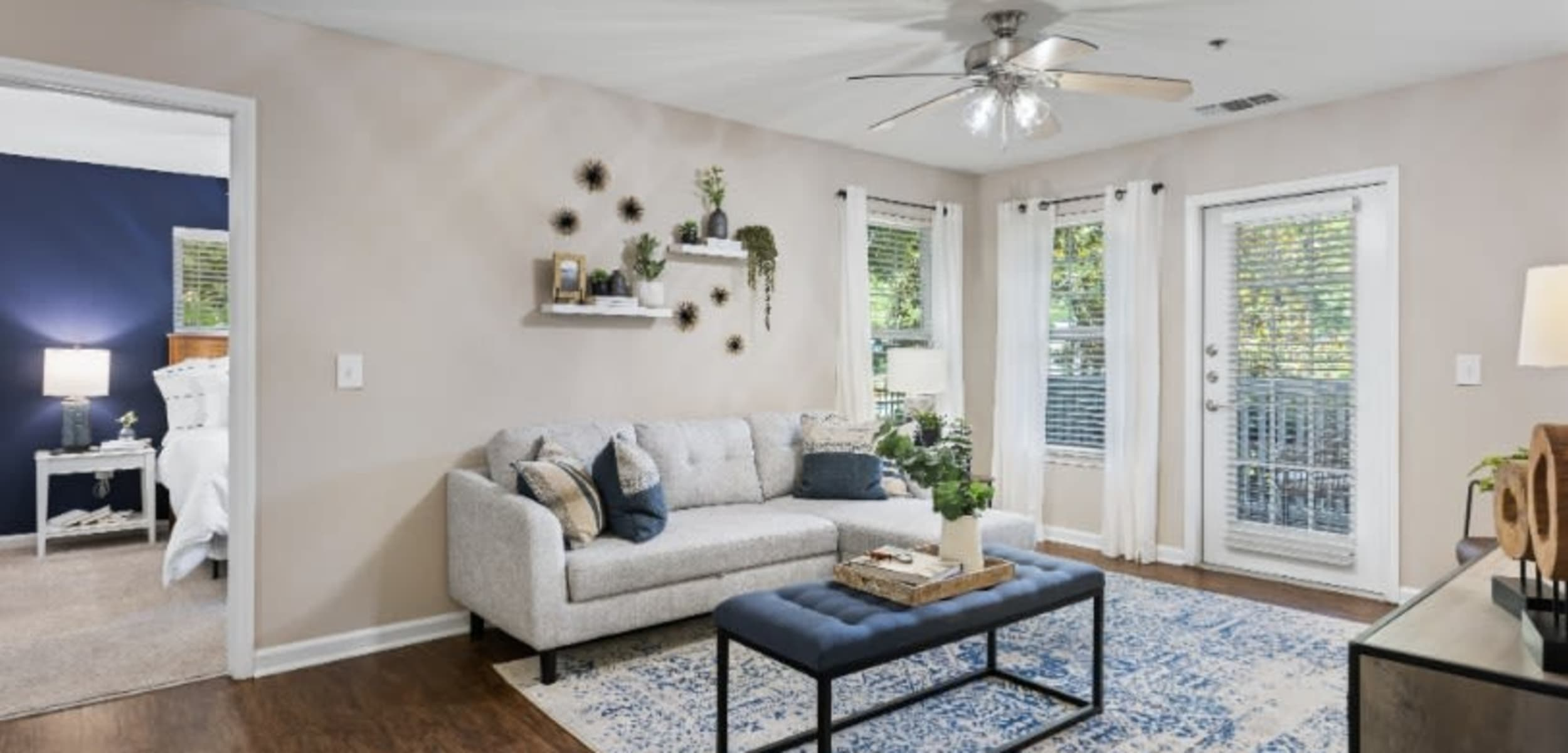 Bright and open living area with wood flooring and ceiling fan at Marquis on Cary Parkway in Morrisville, North Carolina