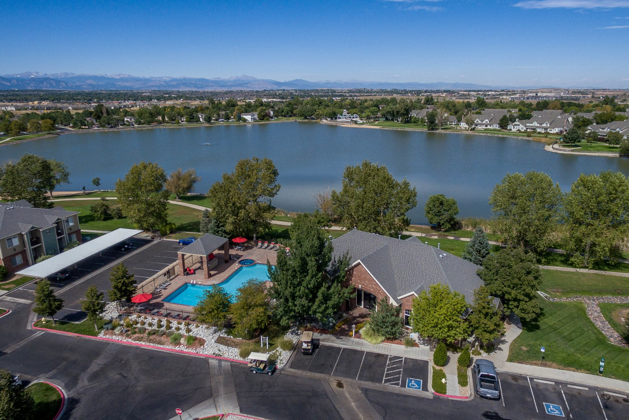 aerial view of lake, leasing office, and pool