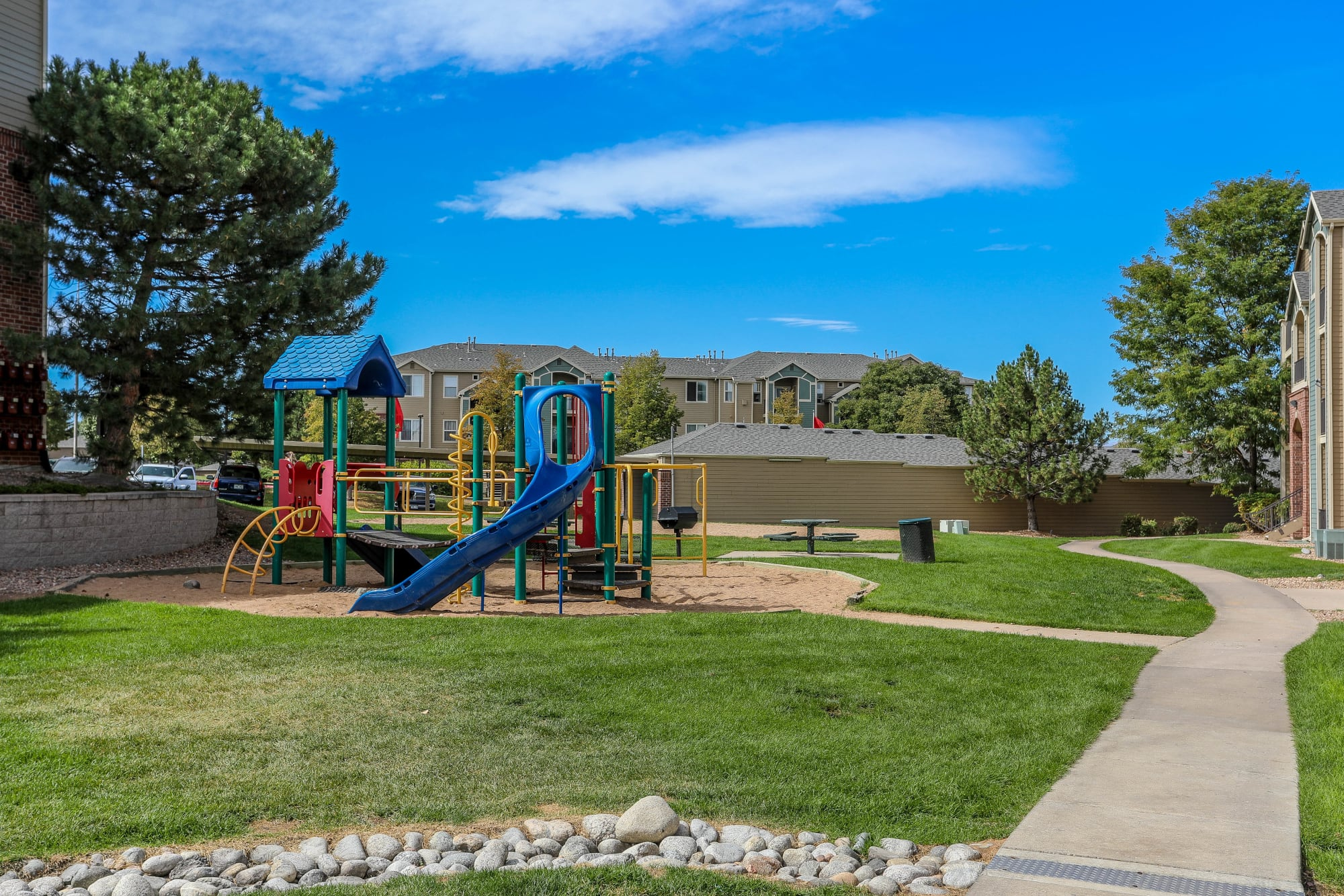 Playground and open landscaping at Promenade at Hunter's Glen Apartments in Thornton, Colorado