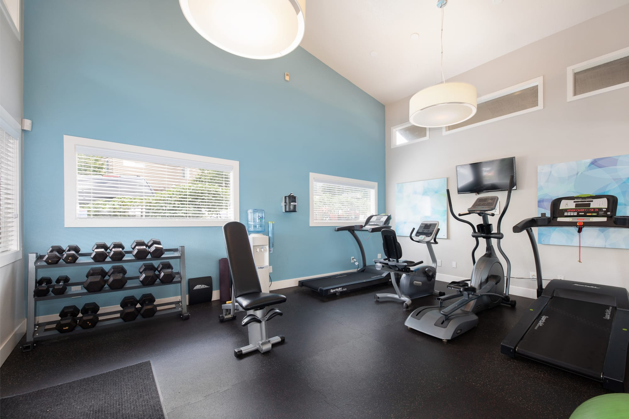 Fitness center with cardio and free weights at Latitude Apartments