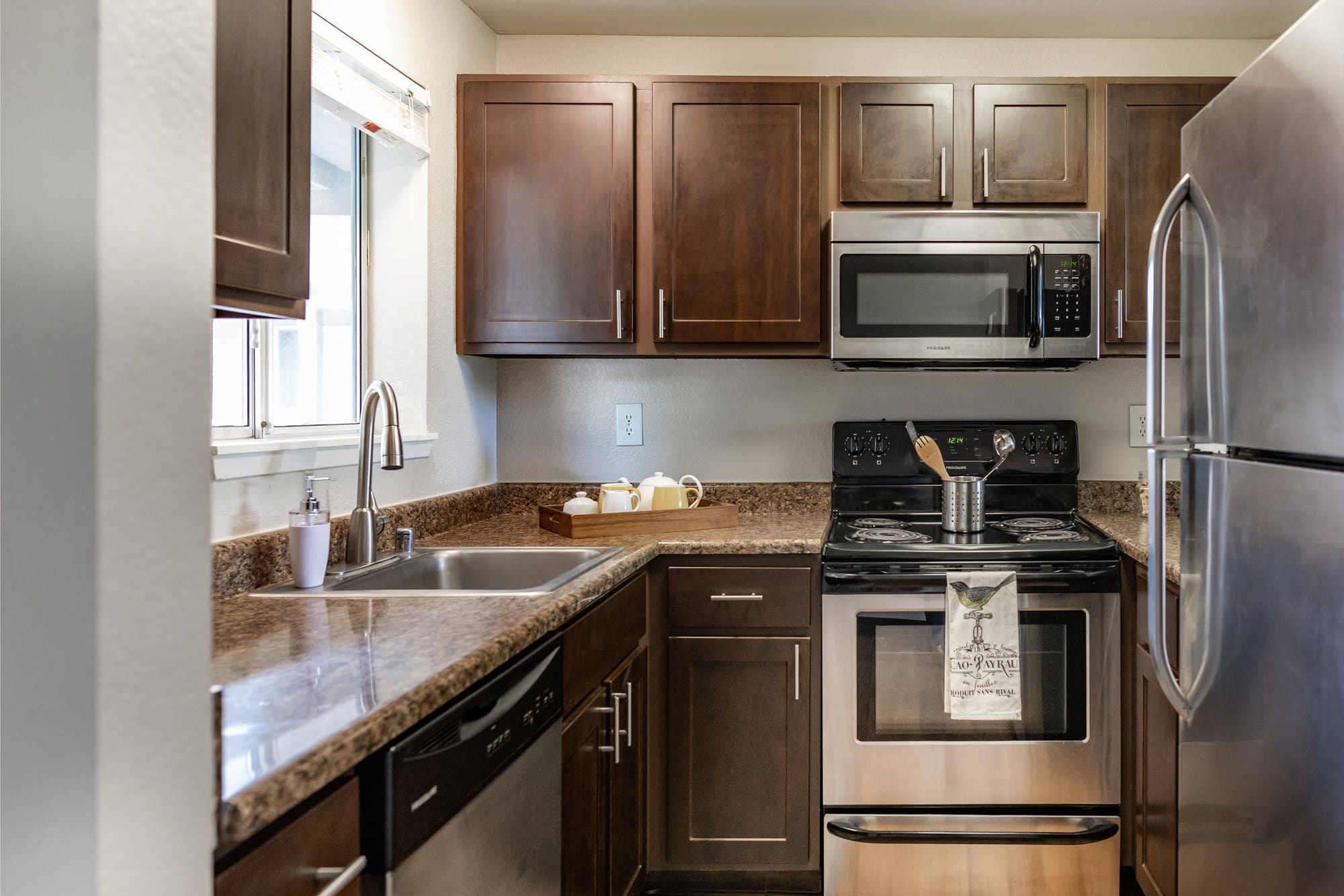 Brown renovated kitchen view with stainless steel appliances At Latitude Apartments