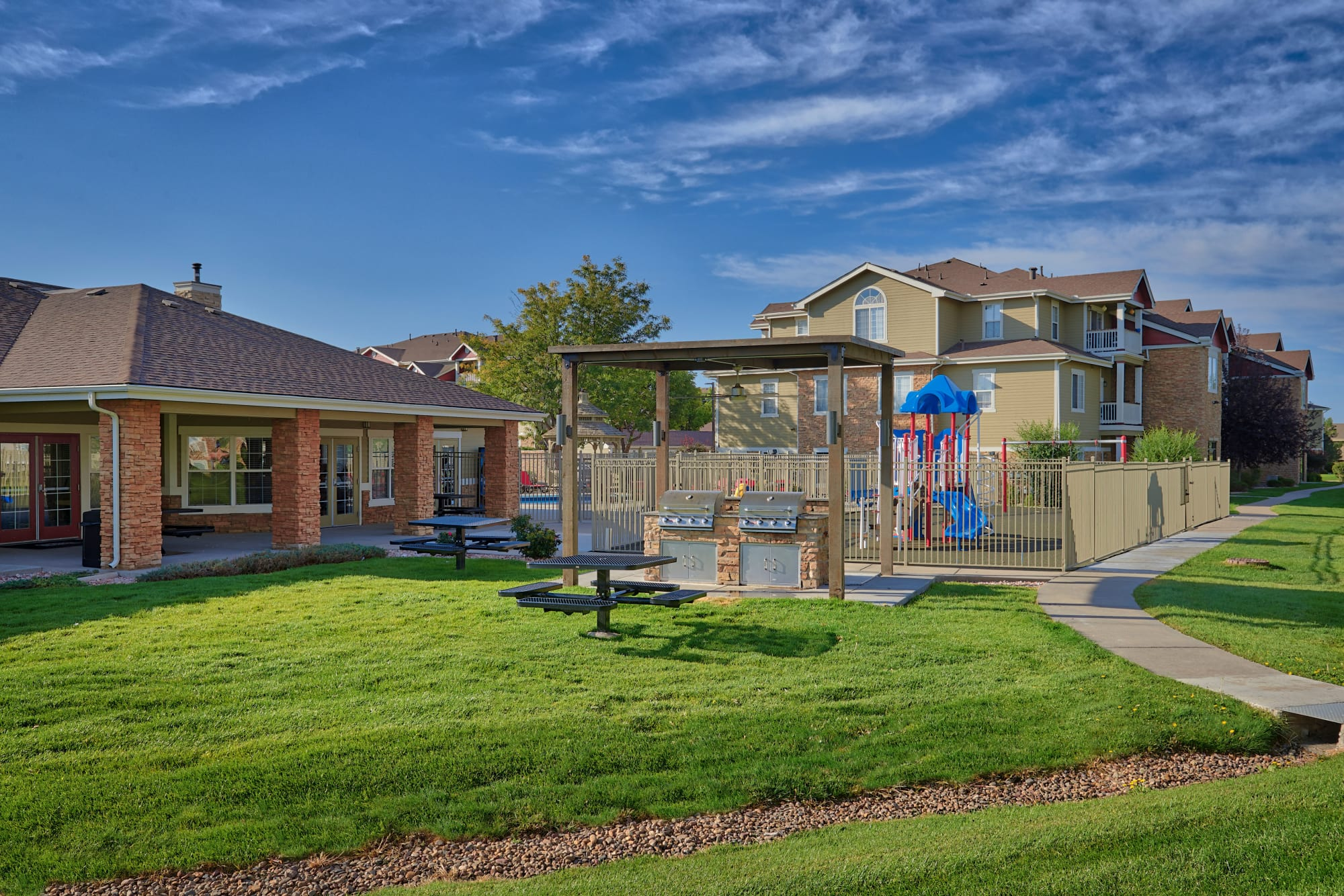 Grilling area surrounded by lush green grass at Westridge Apartments in Aurora, Colorado