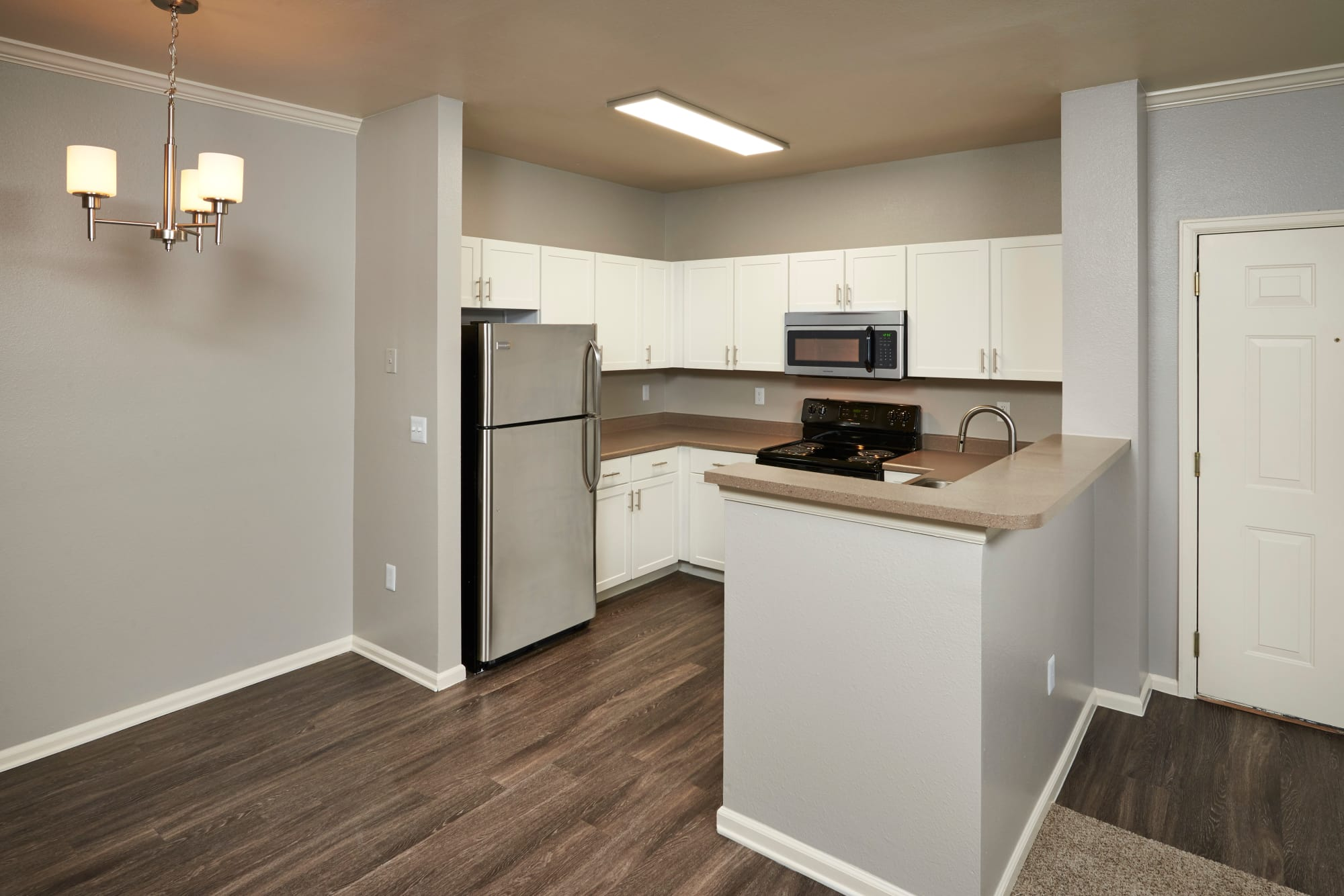 Newly renovated home with white kitchen cabinetry with stainless steel appliances