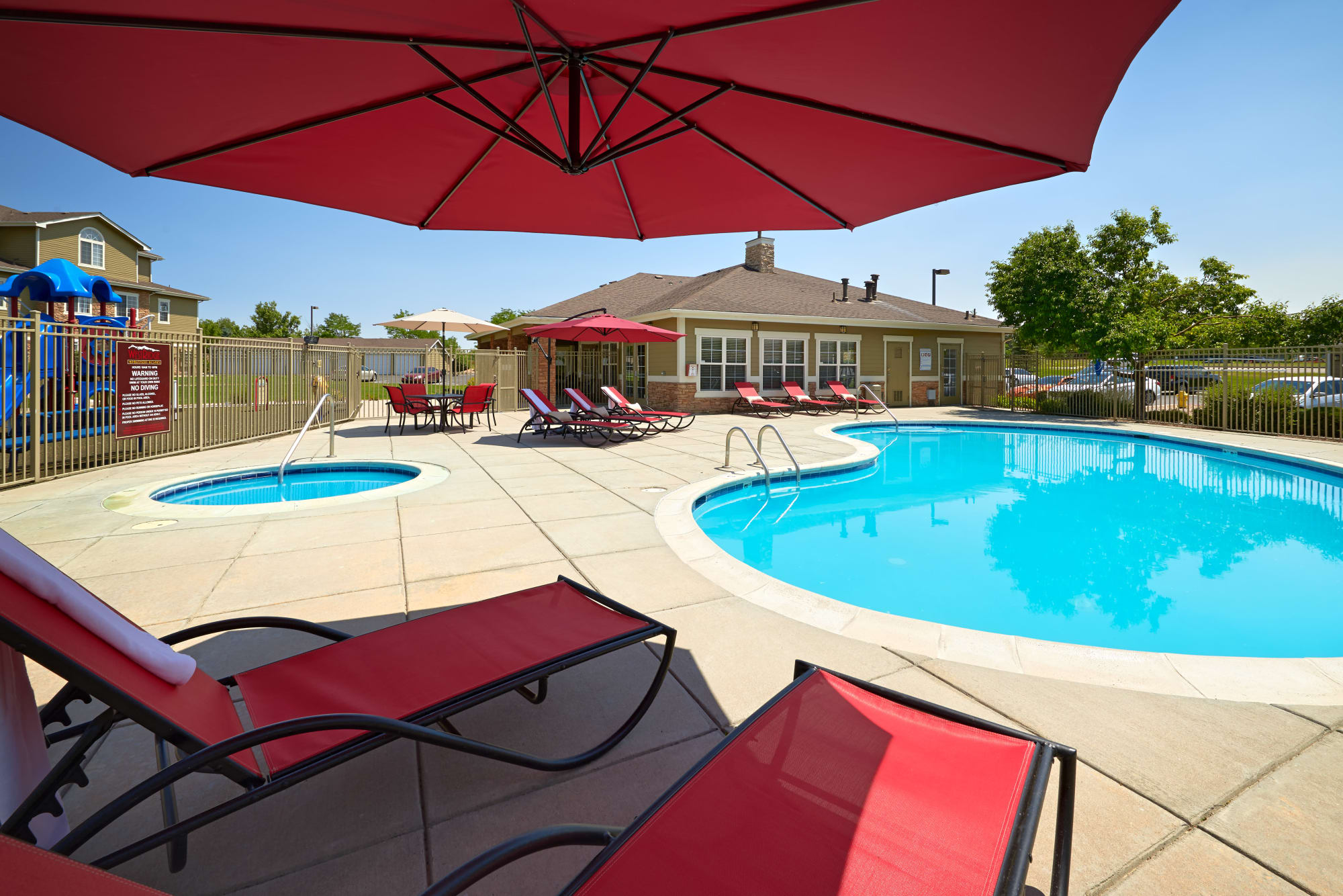 Pool and spa view with lounge chairs and umbrellas at Westridge Apartments in Aurora, CO