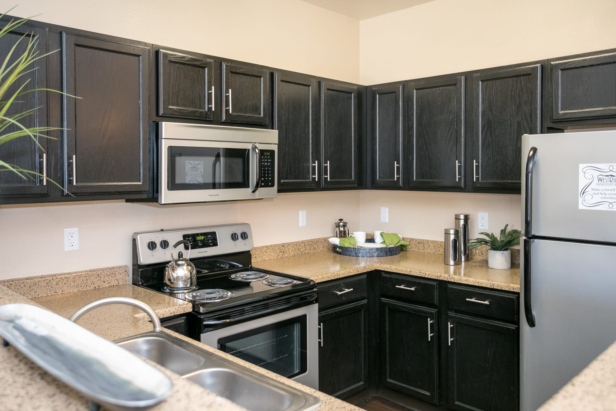 Fully equipped kitchen with dark cabinetry and stainless steel appliances at Westridge Apartments in Aurora, Colorado
