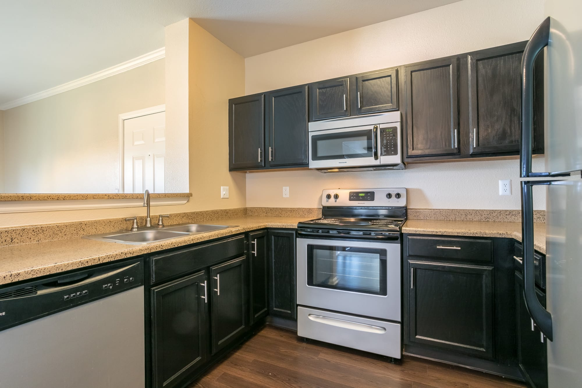 Fully Equipped Kitchen - black cabinetry with stainless steel appliances at Westridge Apartments in Aurora, CO
