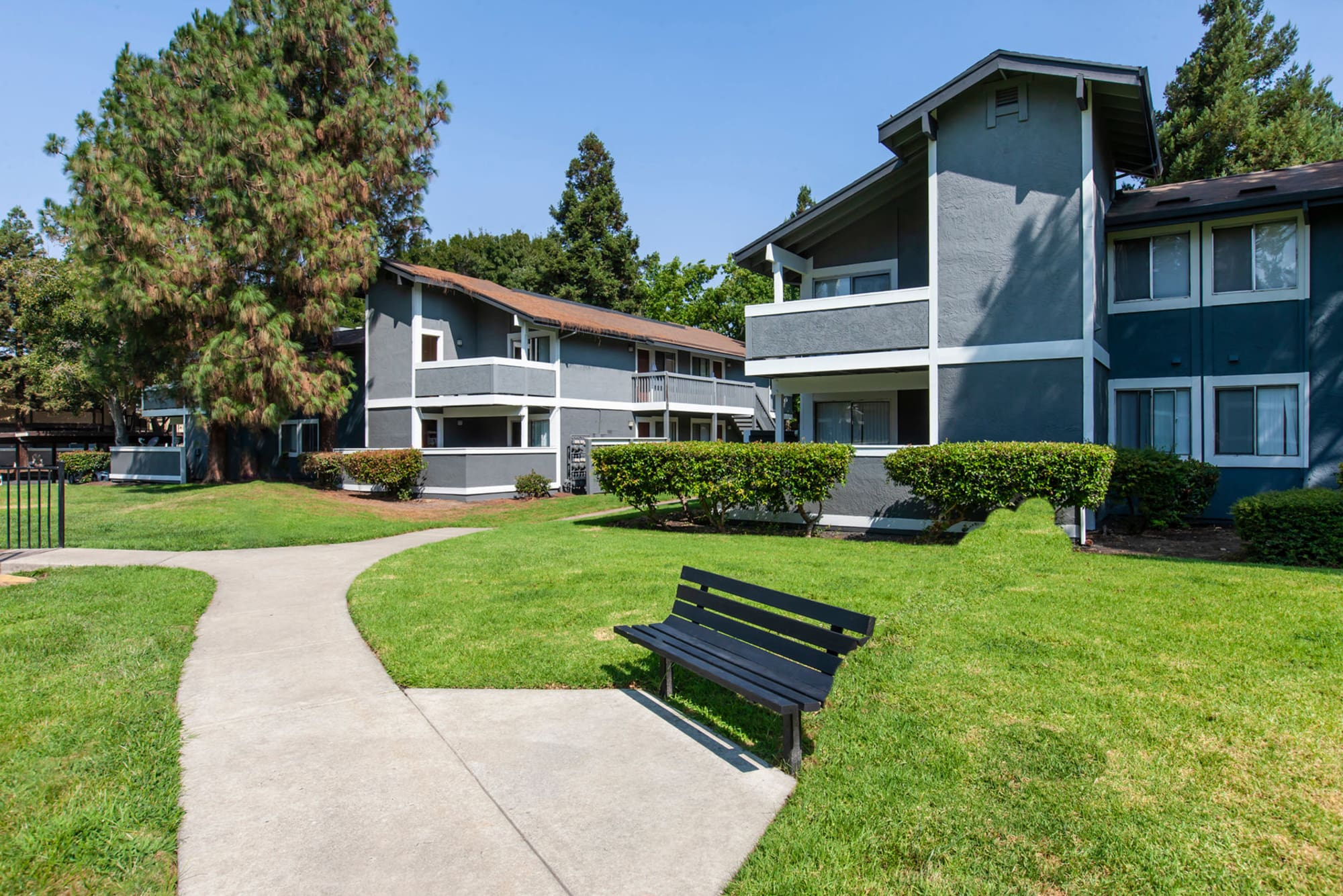 A bench and an open grassy area in front of Avery Park Apartments in Fairfield, California