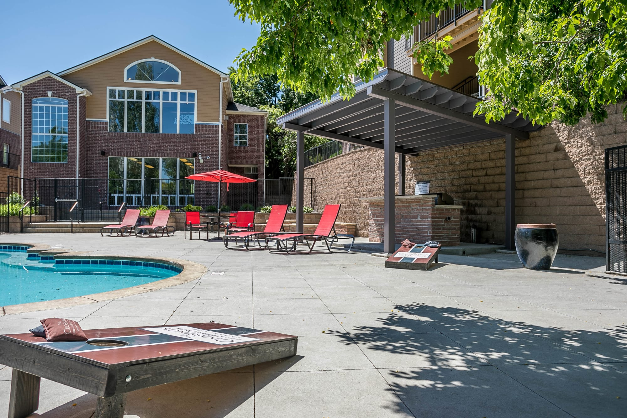 The poolside corn hole boards and covered BBQ area at The Crossings at Bear Creek Apartments in Lakewood, Colorado