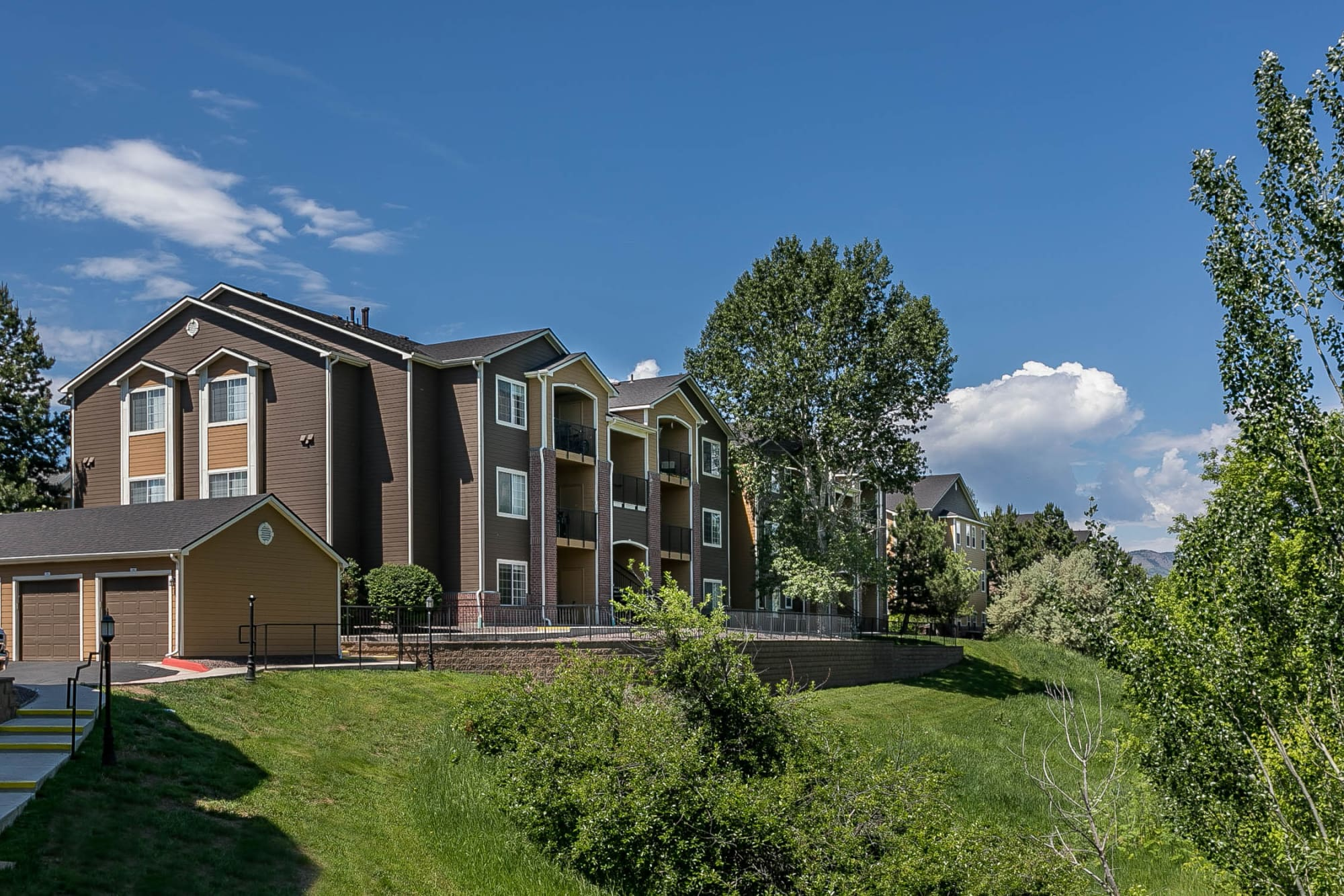 The exterior of the building surrounded by lush landscaping at The Crossings at Bear Creek Apartments in Lakewood, Colorado
