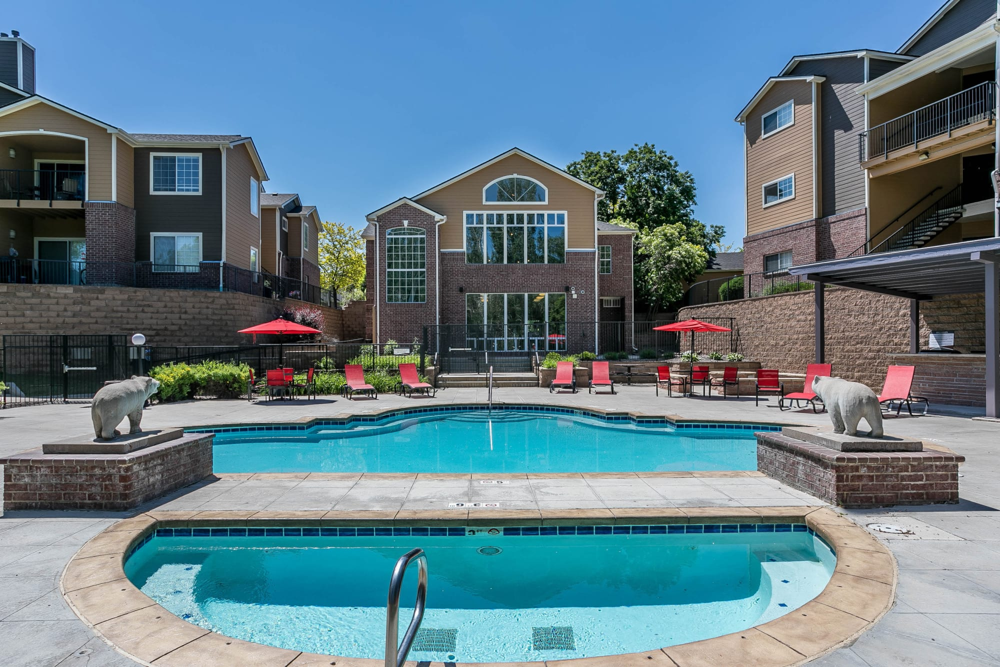 The spa and pool with lounge chairs, umbrellas, BBQ and corn hole at The Crossings at Bear Creek Apartments in Lakewood, Colorado