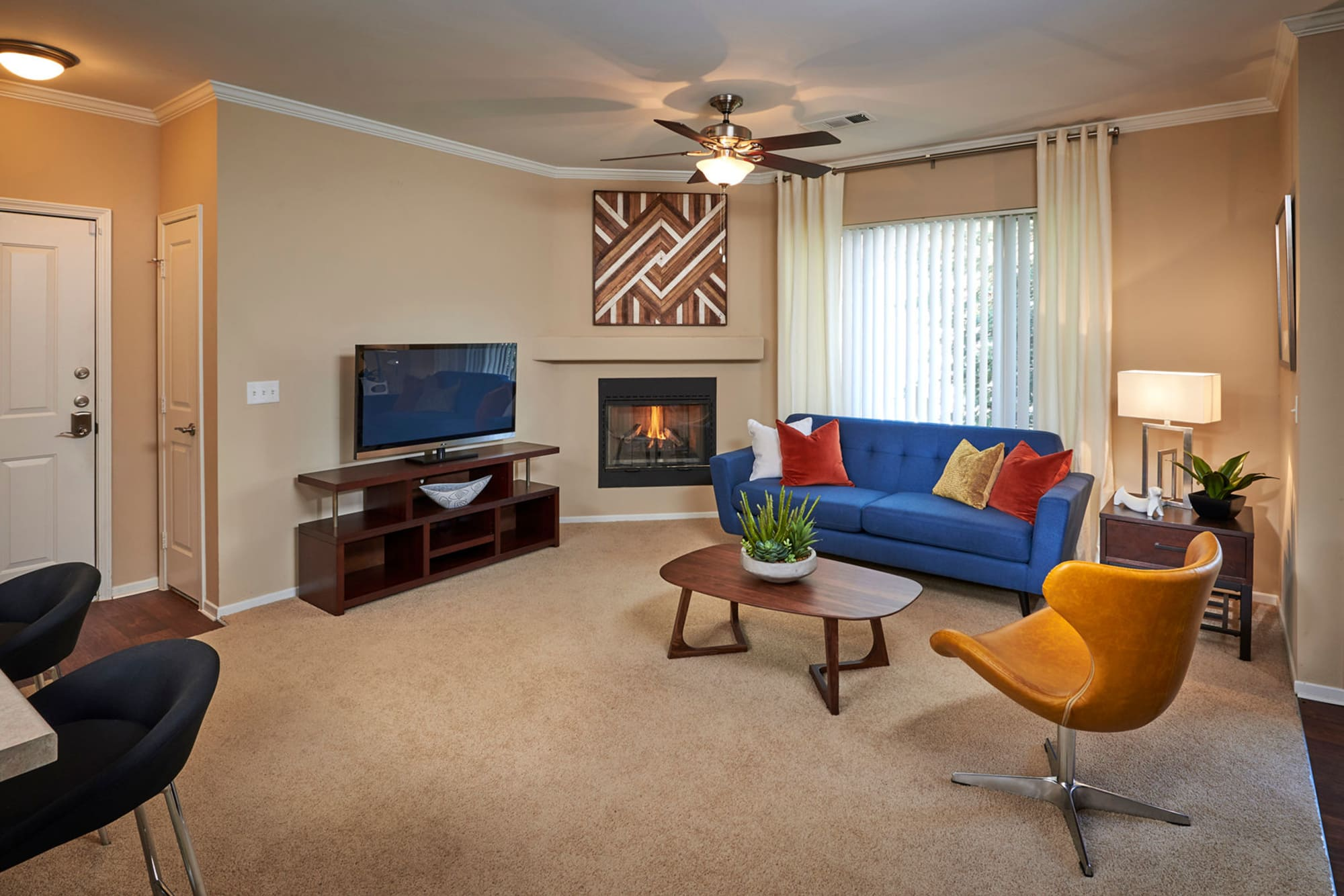 Living room with plush carpeting at Legend Oaks Apartments in Aurora, Colorado