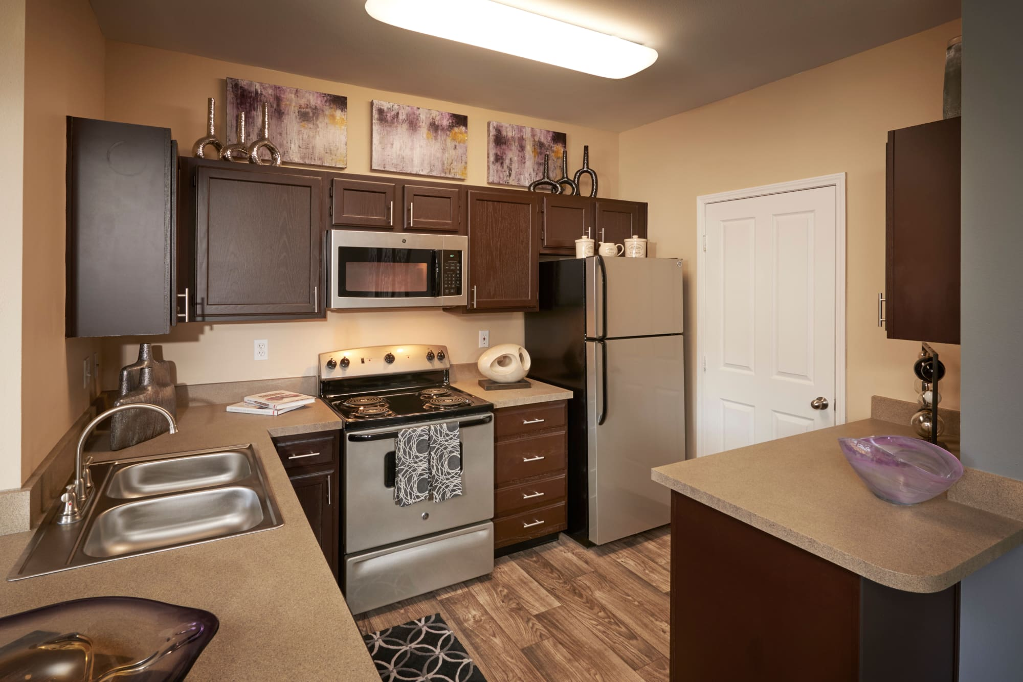 Renovated Kitchen with stainless steel appliances and a breakfast bar at Legend Oaks Apartments in Aurora, Colorado