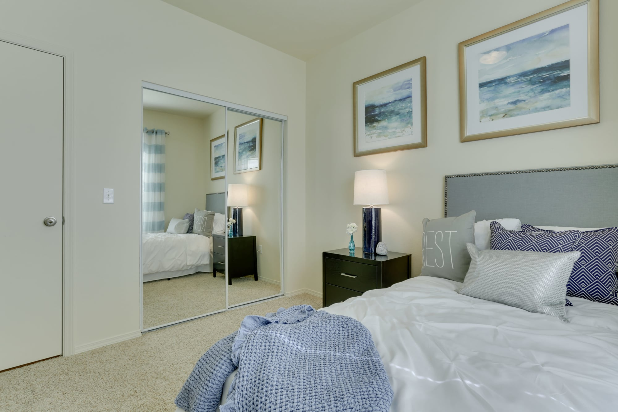 Master bedroom with mirrored closet door at The Landings at Morrison Apartments in Gresham, Oregon