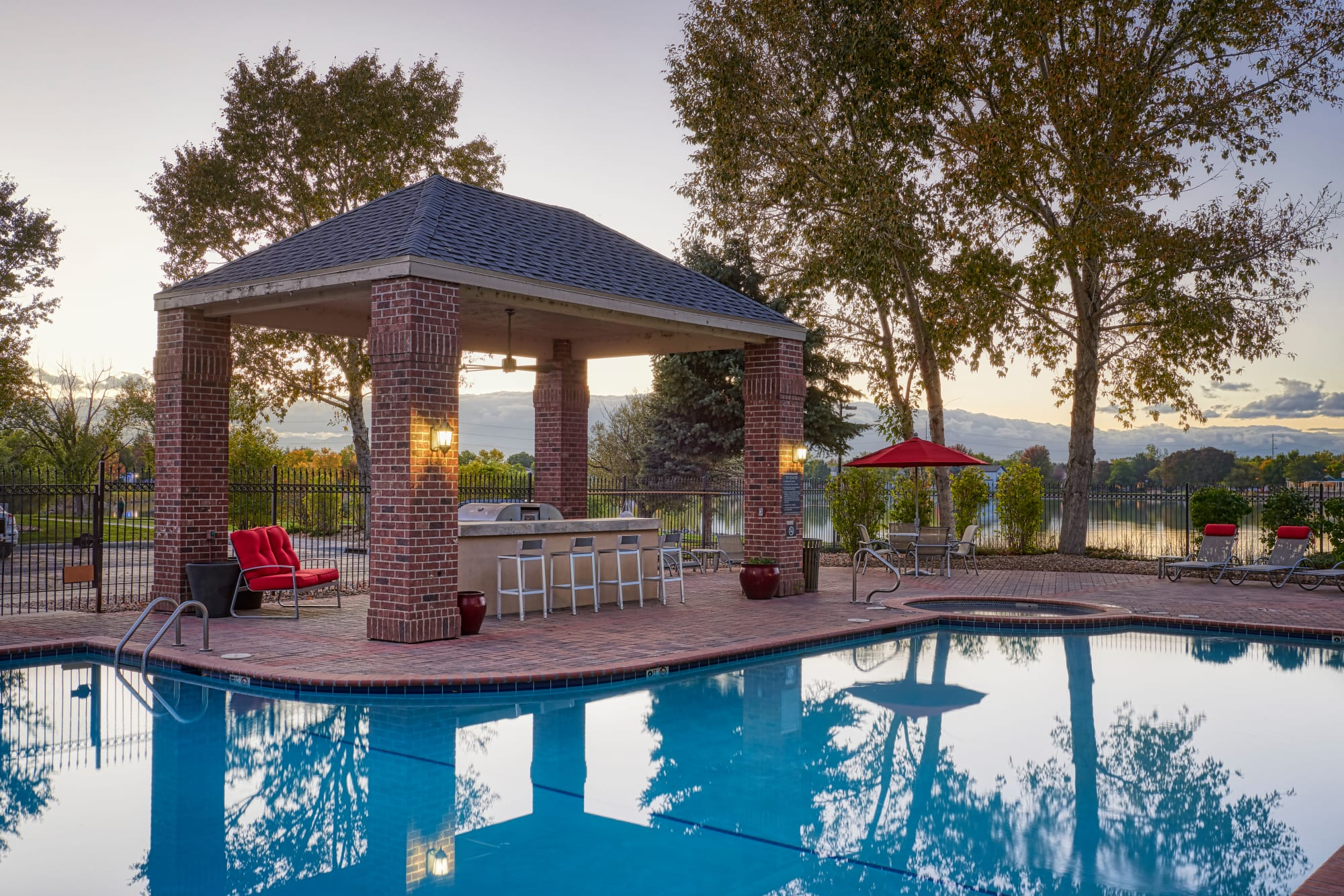 Poolside covered BBQ area at sunset at Promenade at Hunter's Glen Apartments in Thornton, Colorado