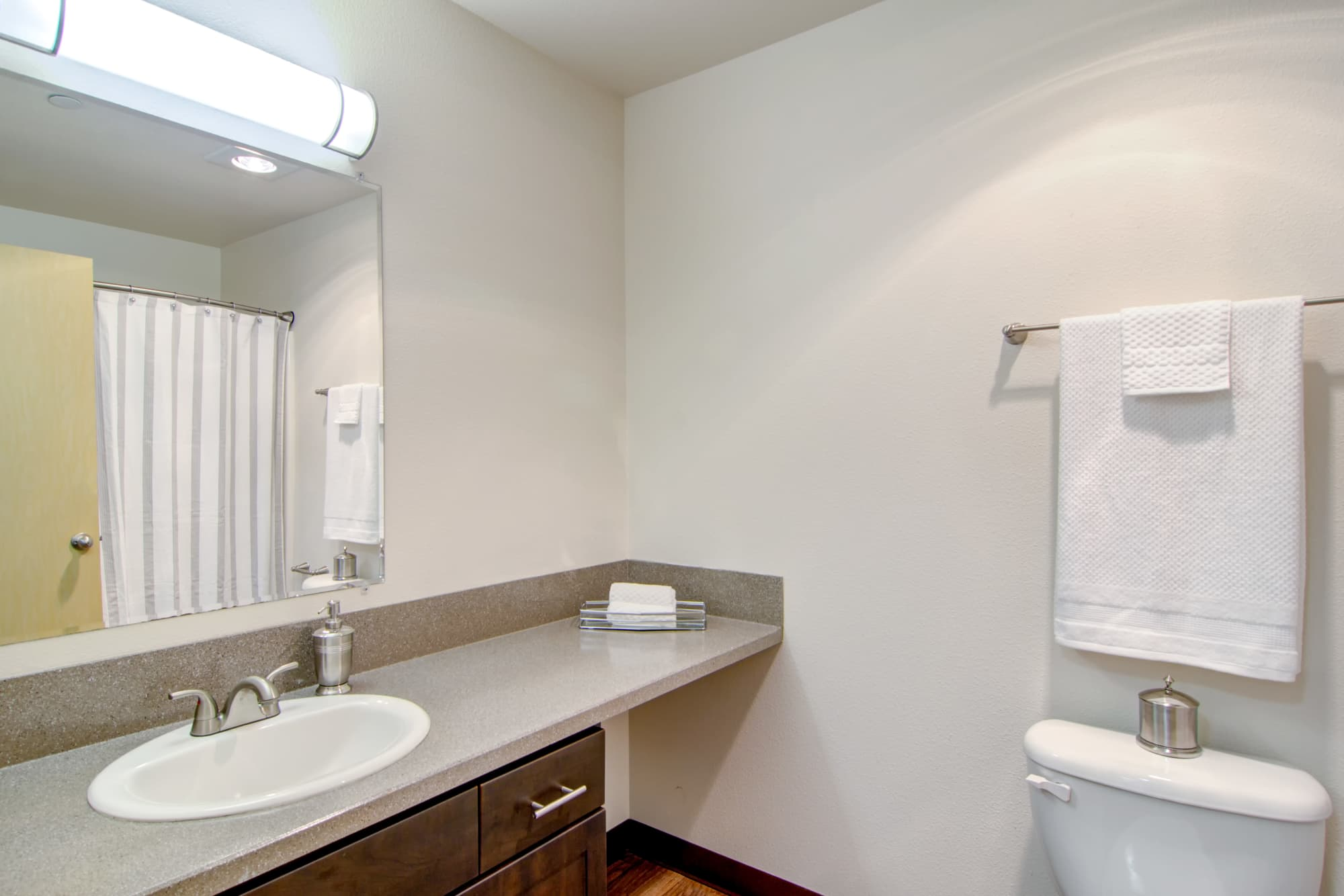 Renovated bathroom with brown cabinets at The Addison Apartments in Vancouver, Washington