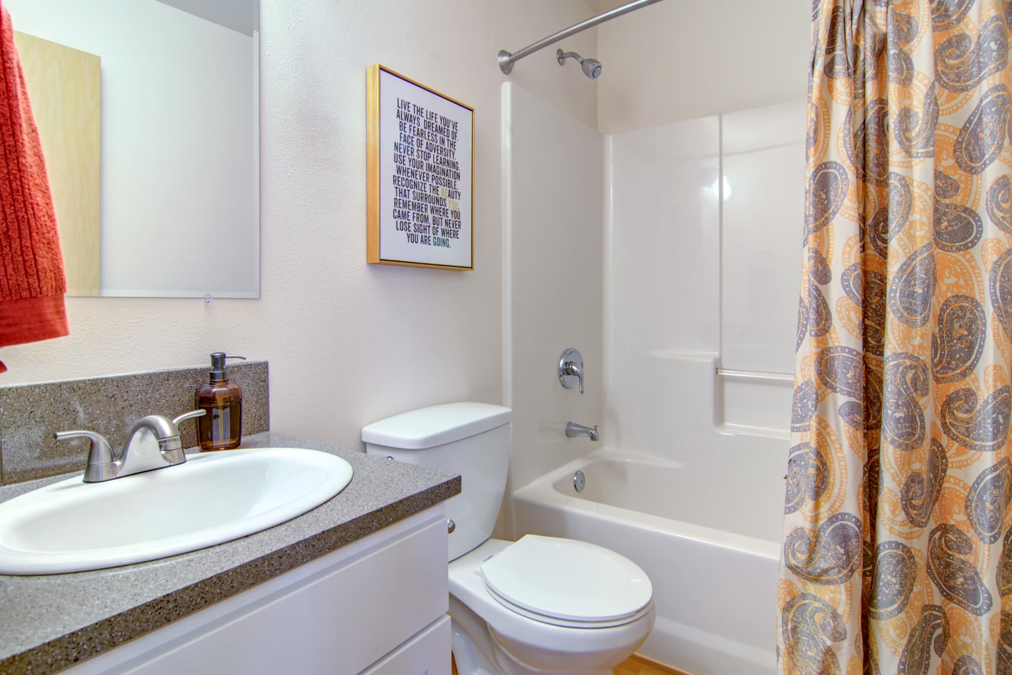 Renovated bathroom with white cabinets and a bathtub at The Addison Apartments in Vancouver, Washington