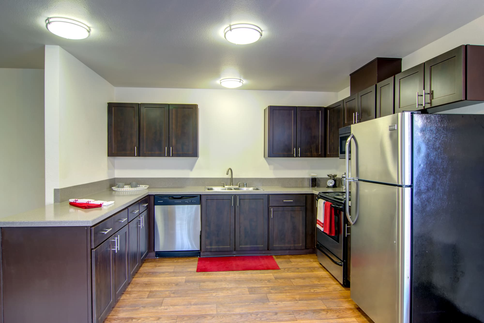brown Kitchen renovation with stainless steel appliances at The Addison Apartments