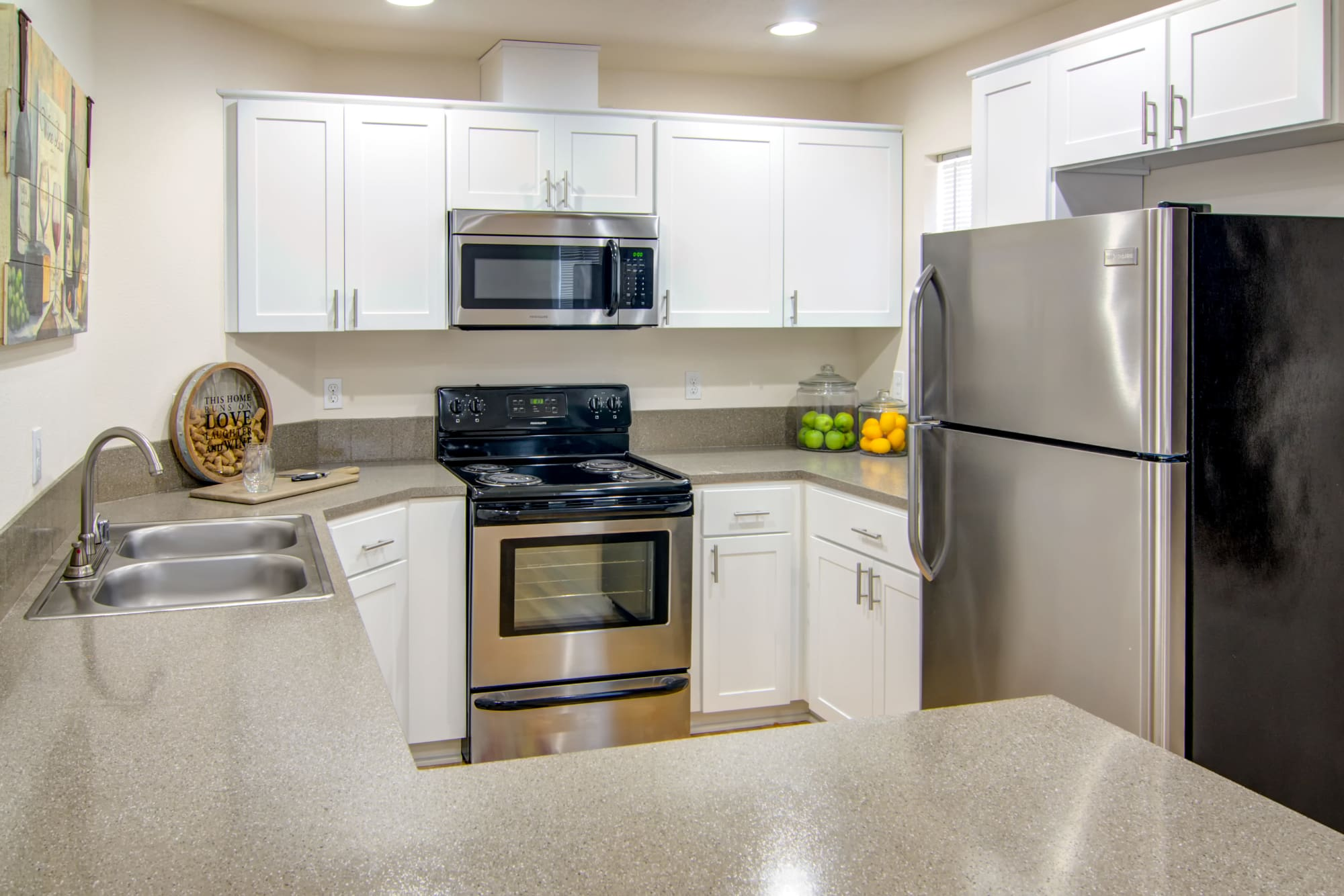 White kitchen with stainless steel appliances at The Addison Apartments in Vancouver, Washington