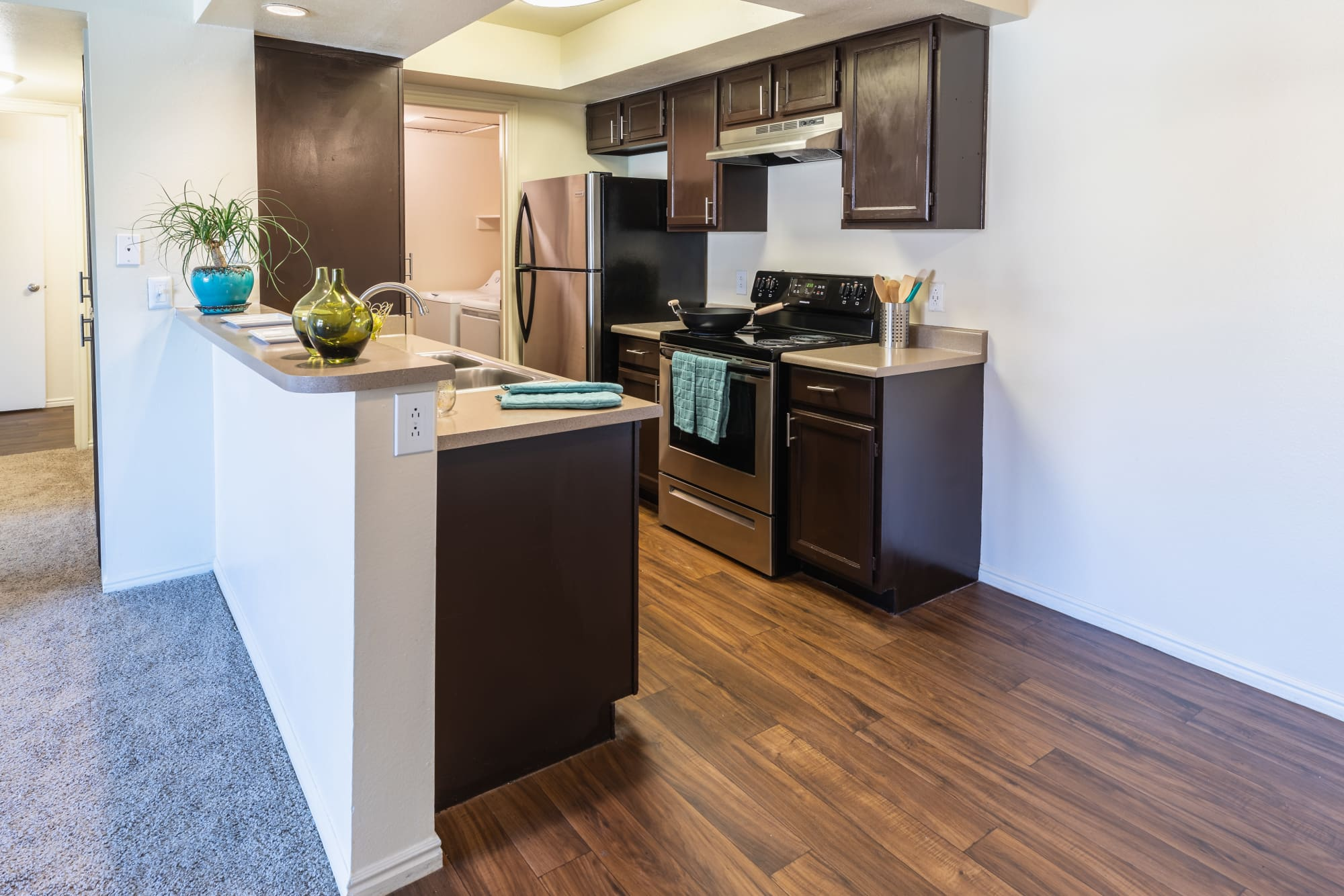 Fully Equipped Renovated Brown Kitchen and Dining Room with Stainless Steel Appliances at Shadowbrook Apartments in West Valley City, UT