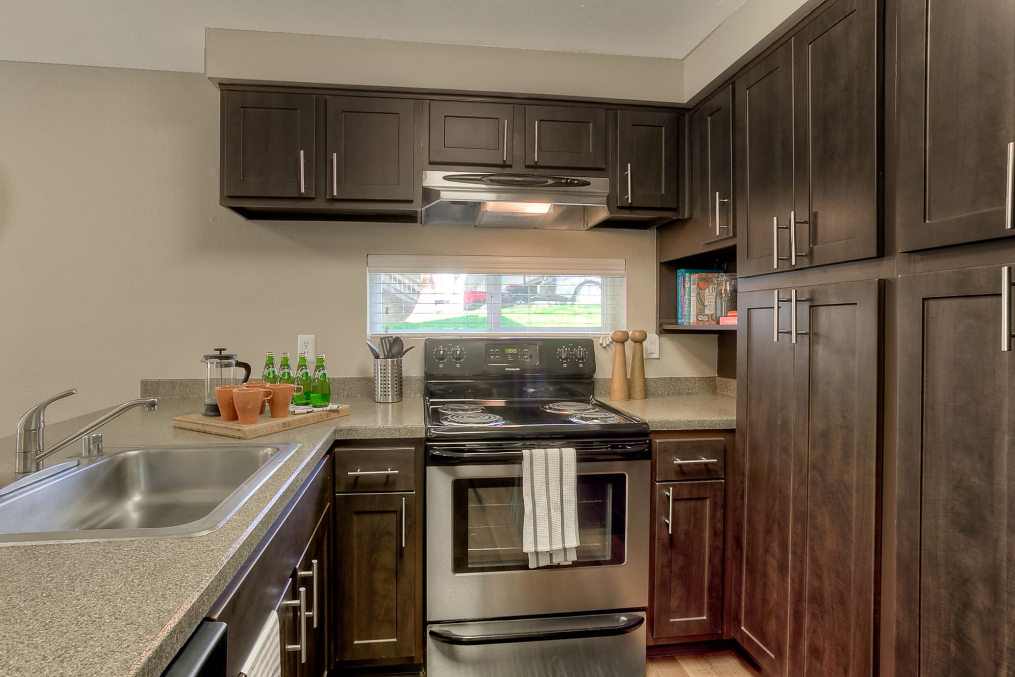 Renovated kitchen with brown cabinets at Park South Apartments in Seattle, Washington