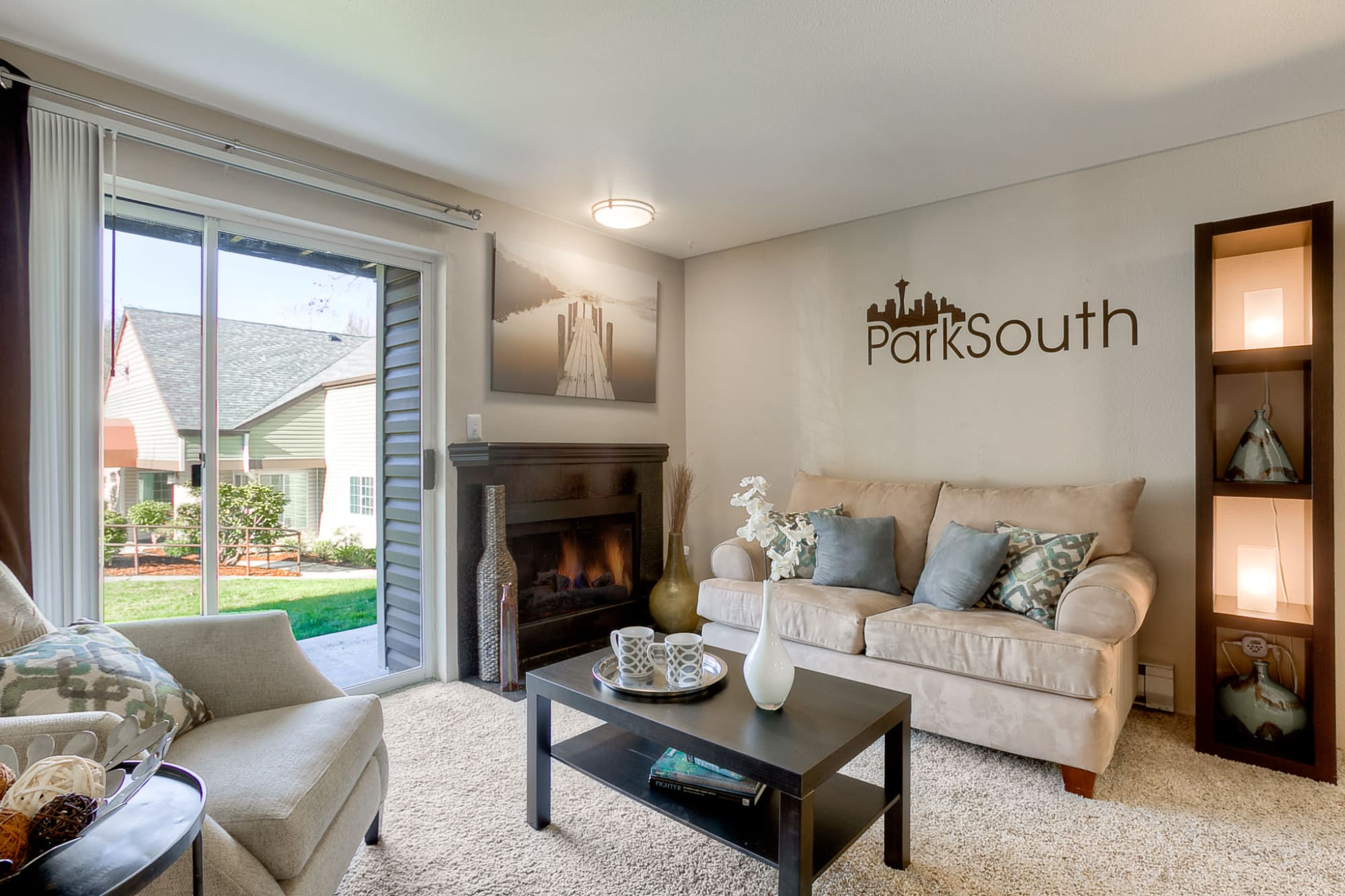 Sunny living room with a fireplace at Park South Apartments in Seattle, Washington