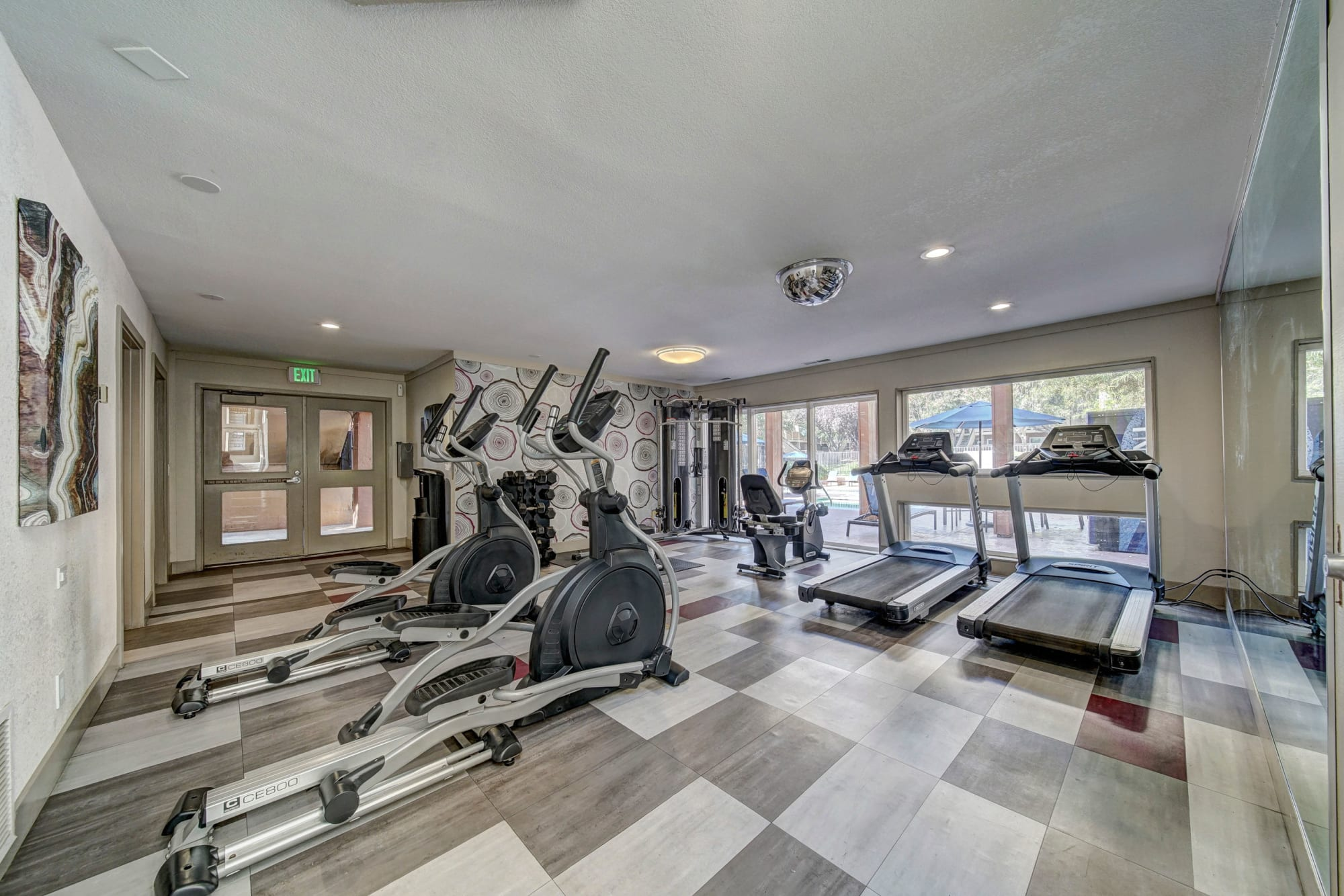 Fitness center with cardio machines and large windows looking out to the pool area at The Timbers Apartments in Hayward, California