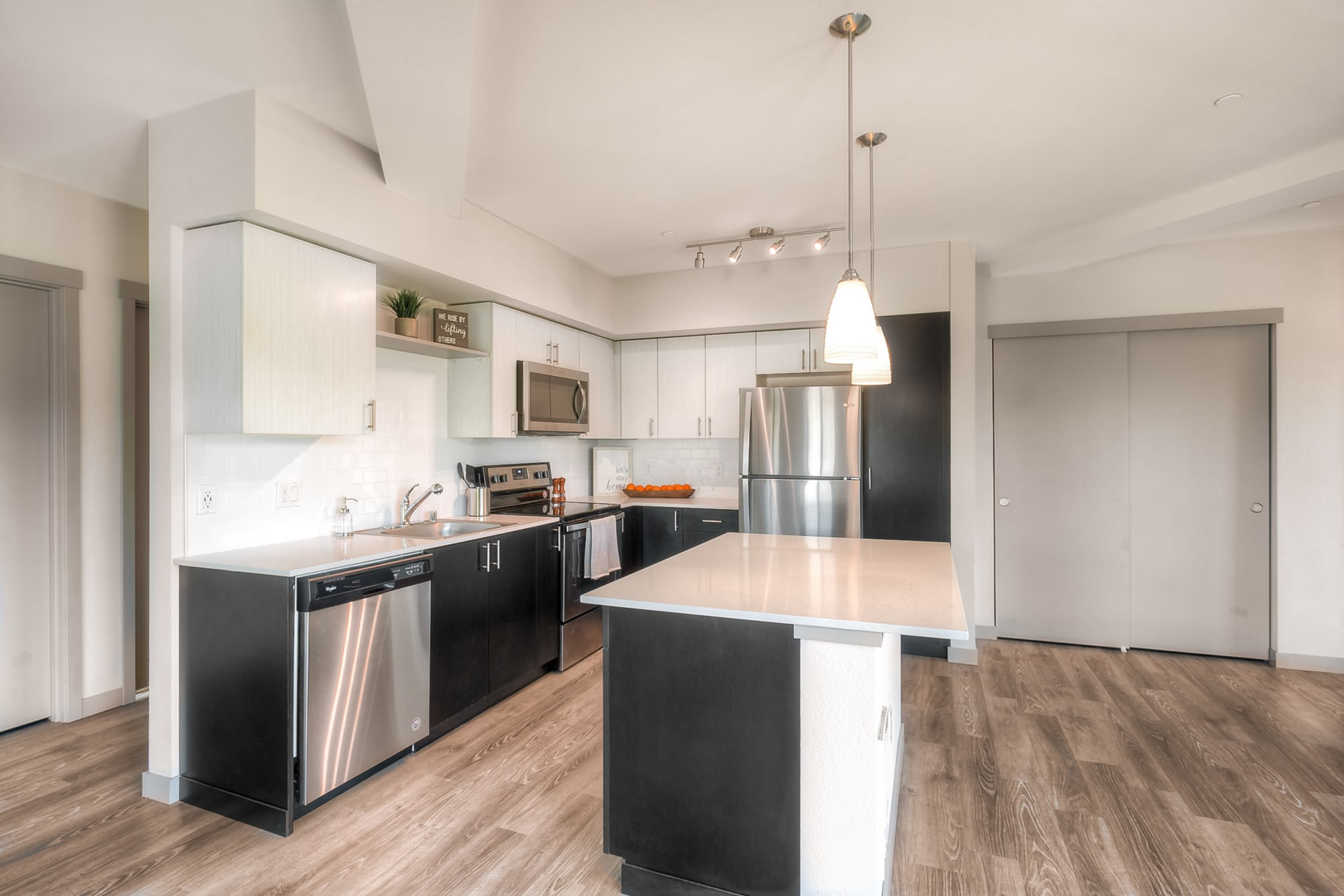 beautiful spacious Kitchen with an island and quartz counters inside of Tria Apartmentsin Newcastle