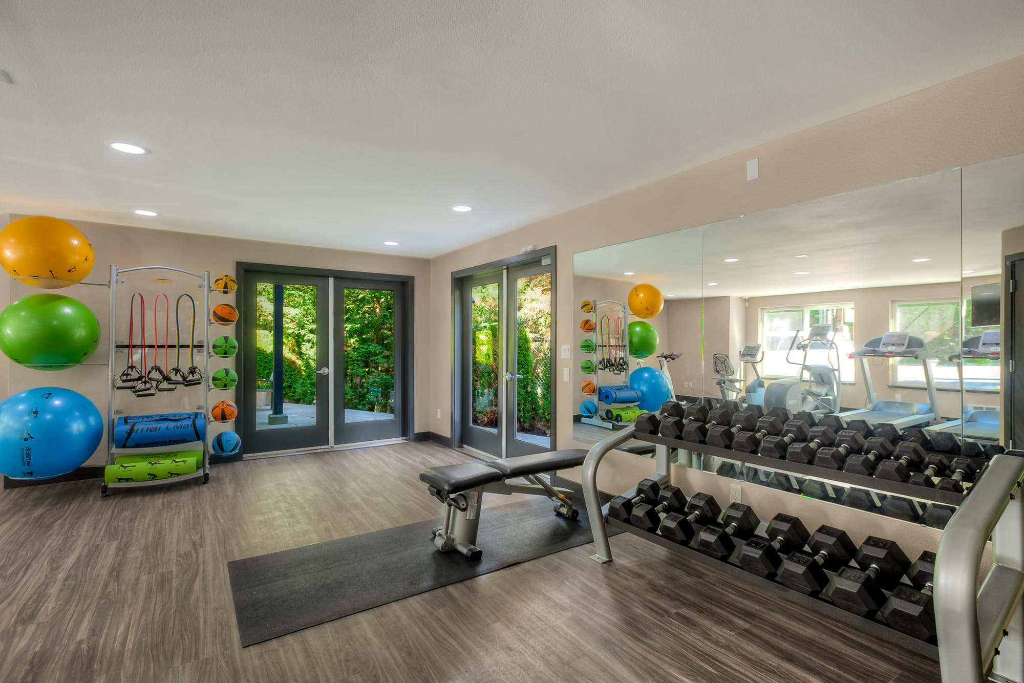 Newly renovated fitness center with free weights at Karbon Apartments in Newcastle, Washington