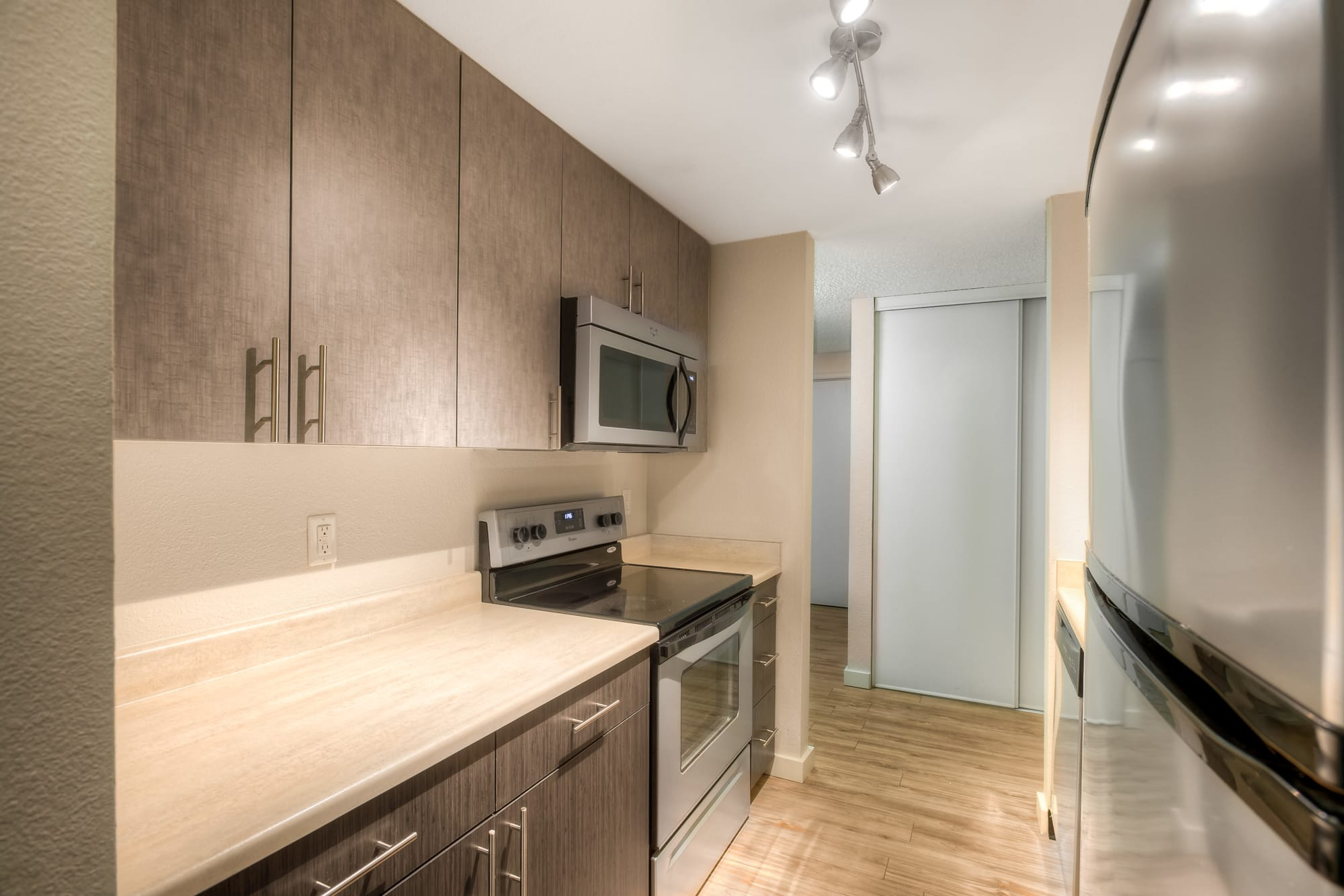 brown kitchen with stainless steel appliances at Karbon Apartments
