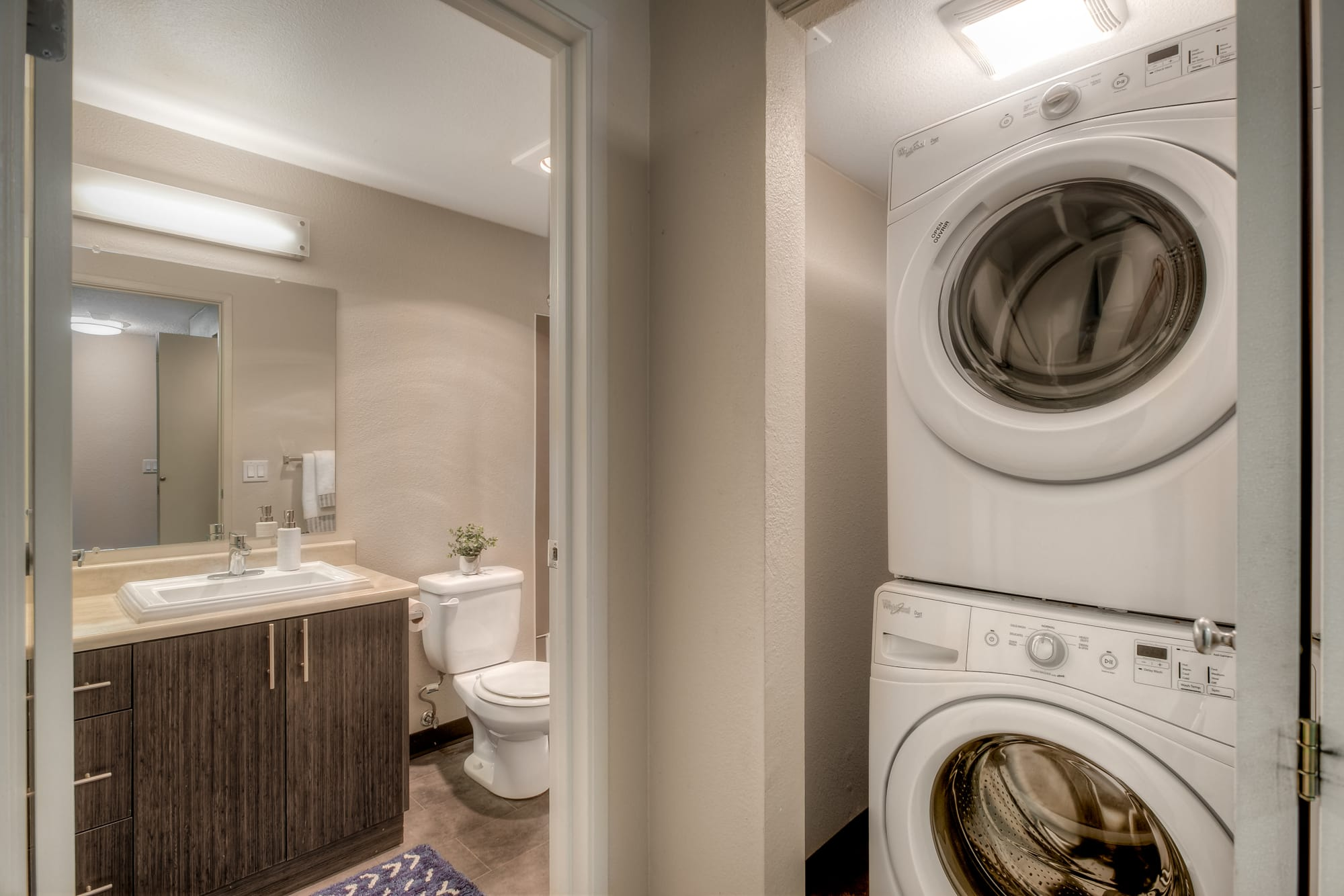 Bathroom and stacked washer and dryer at Karbon Apartments in Newcastle, Washington
