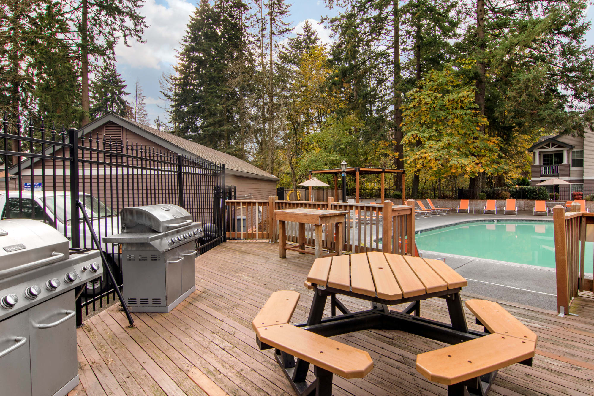 outdoor bbq area with seating, poolside At Autumn Chase Apartments