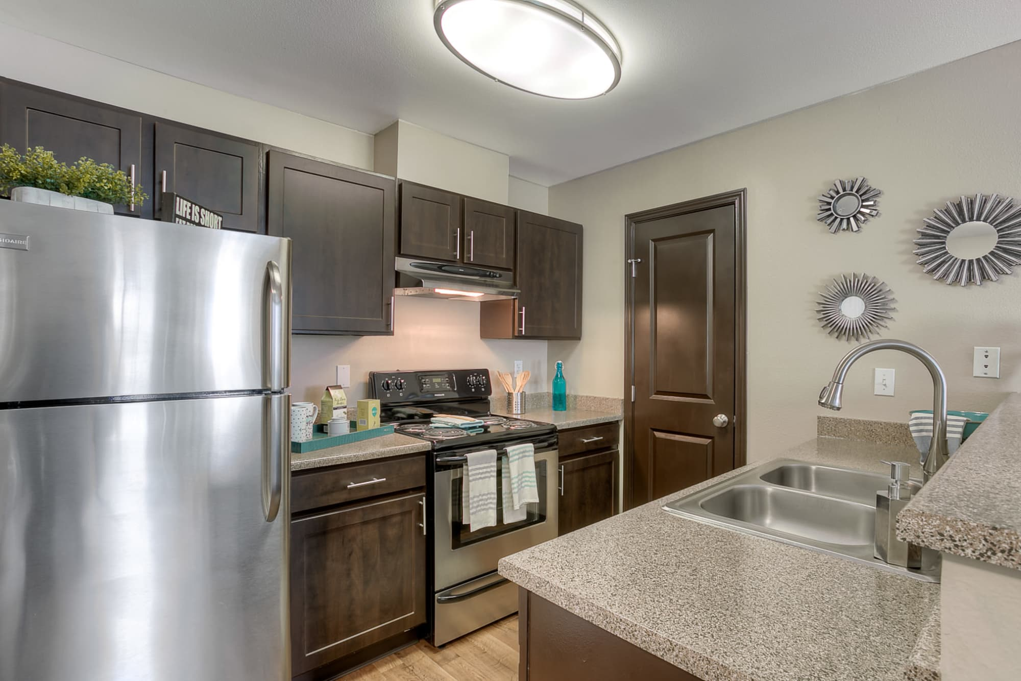 Brown Renovated Model Kitchen with stainless steel appliances at Pebble Cove Apartments in Renton
