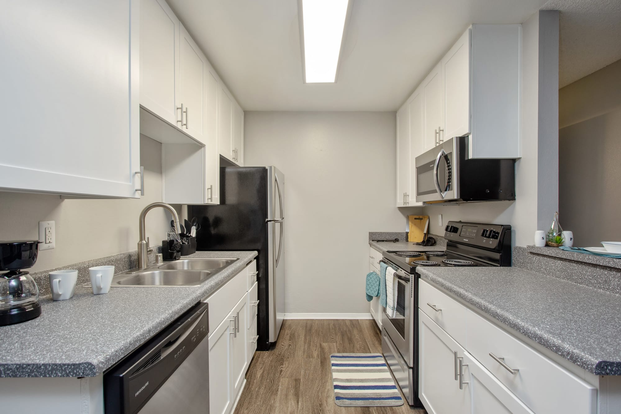 White renovated kitchen with stainless steel appliances at Shadow Ridge Apartments in Oceanside, California