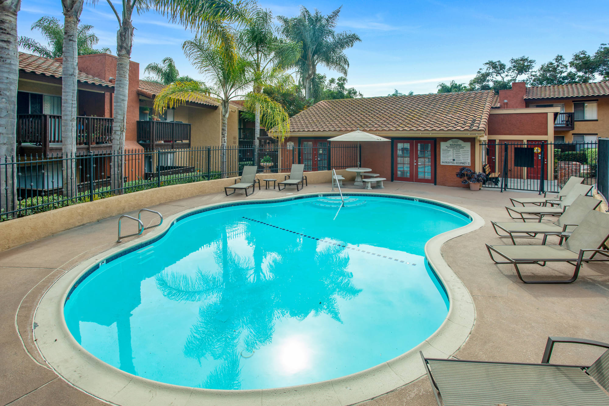 Pool view with lounge chairs and exterior of leasing office