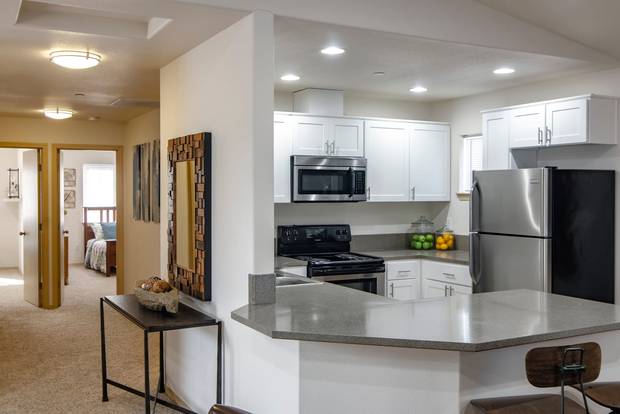 Renovated kitchen with white cabinets and a hallway view at The Addison Apartments in Vancouver, Washington