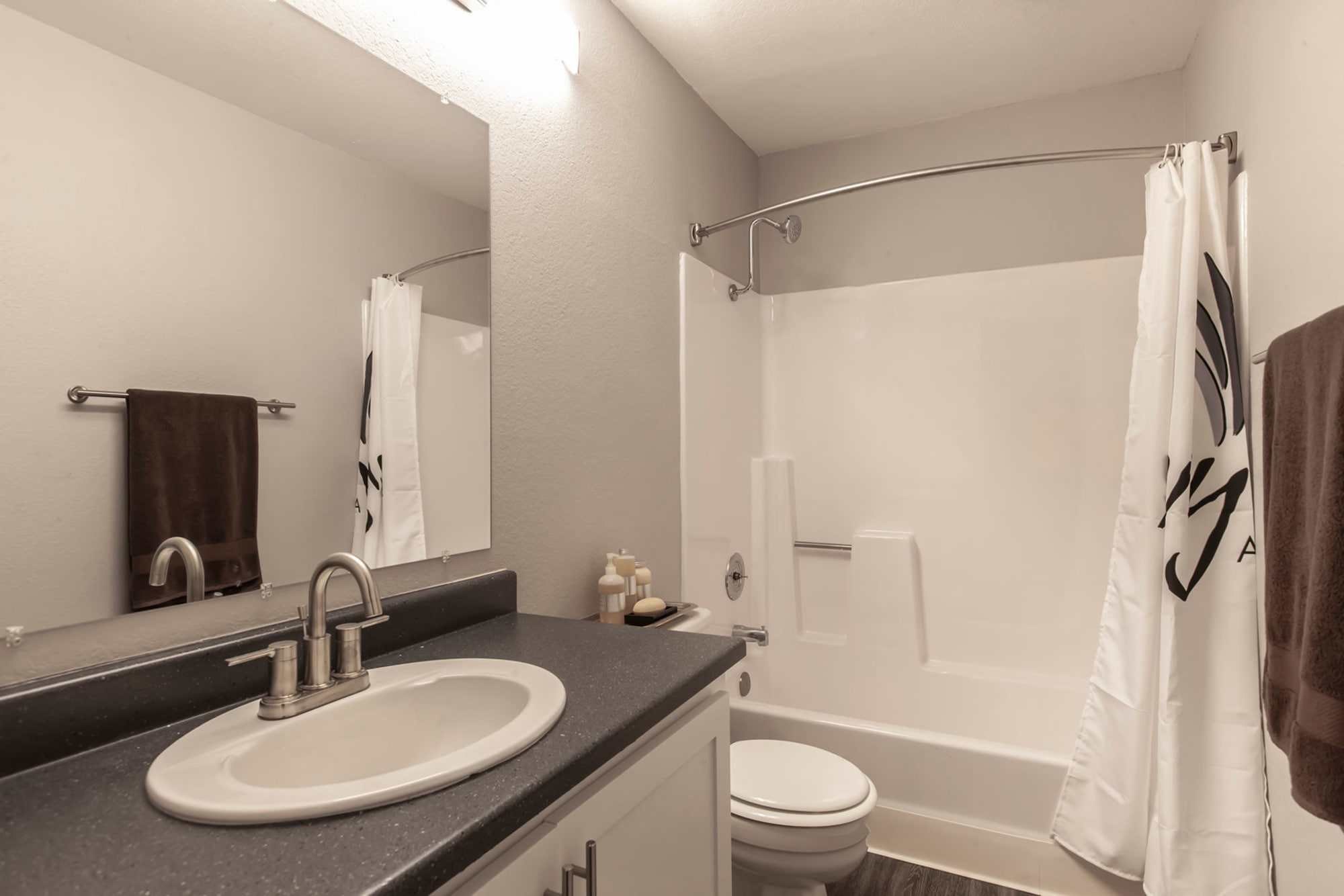 A renovated bathroom with white cabinetry and a tub at Avery Park Apartments in Fairfield, California