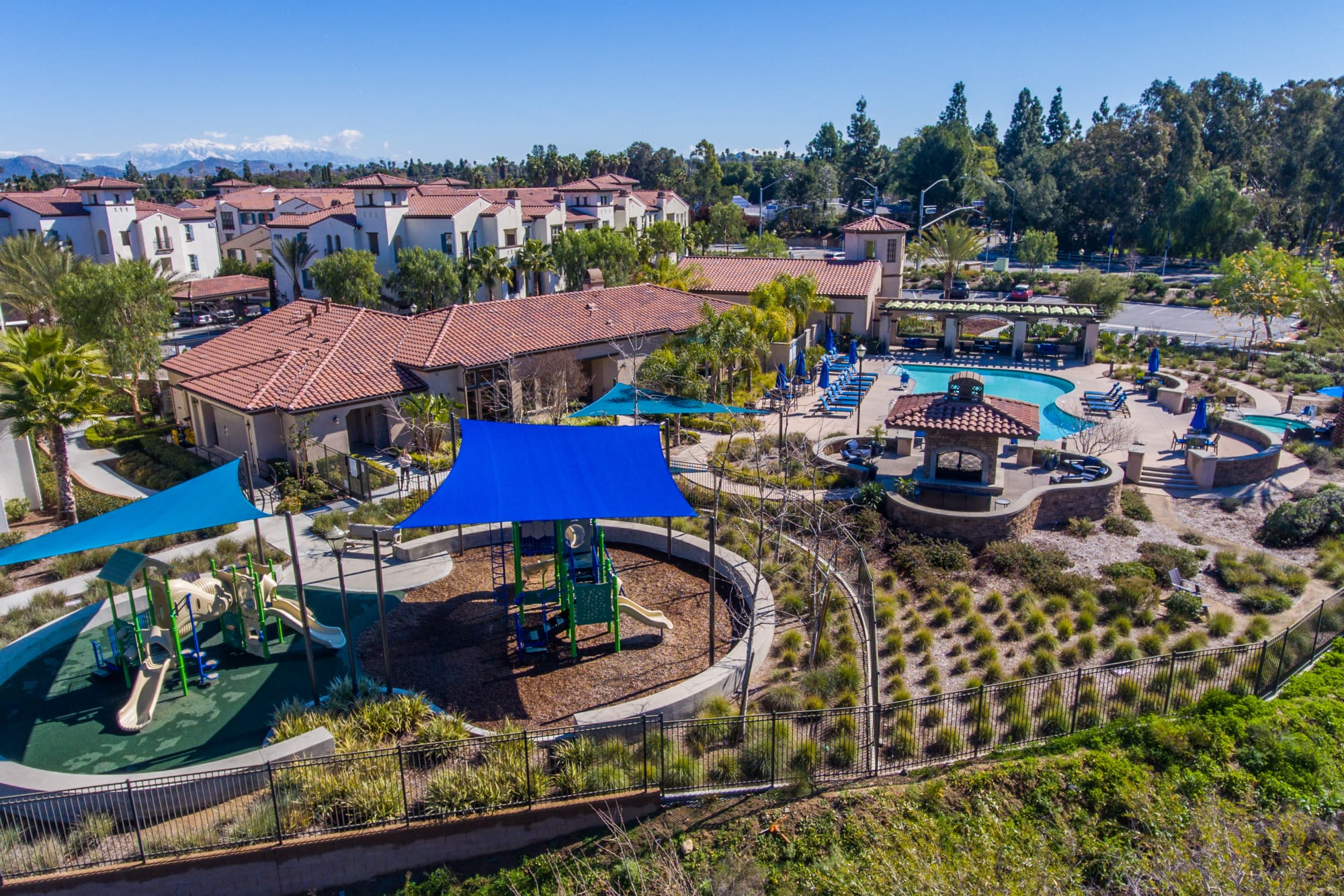 Aerial view of pool, playground, and property with surrounding area at Palisades Sierra Del Oro