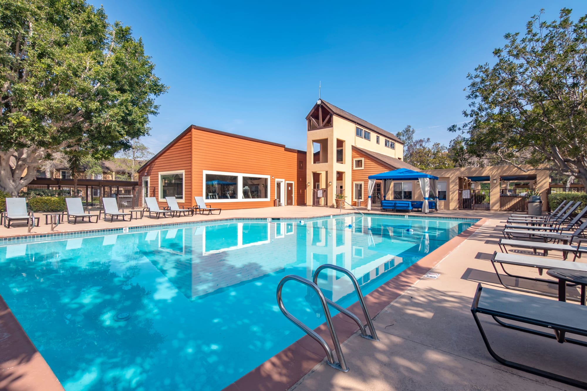 Swimming Pool and Deck with lounge chairs and umbrellas at Terra Nova Villas in Chula Vista, CA