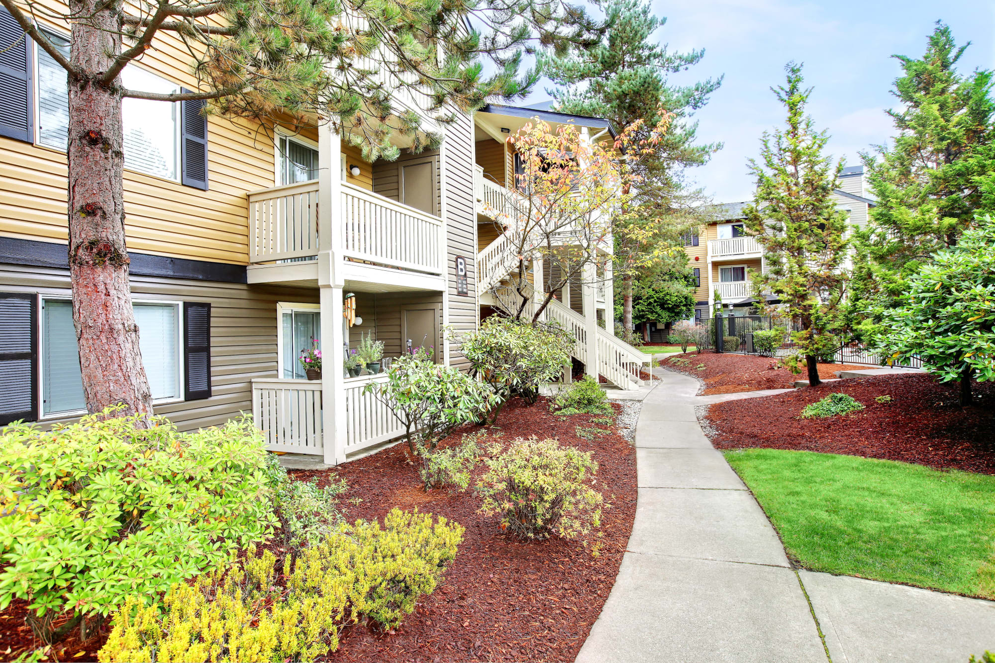 Exterior Buildings and beautifully landscaped walkway at Newport Crossing Apartments