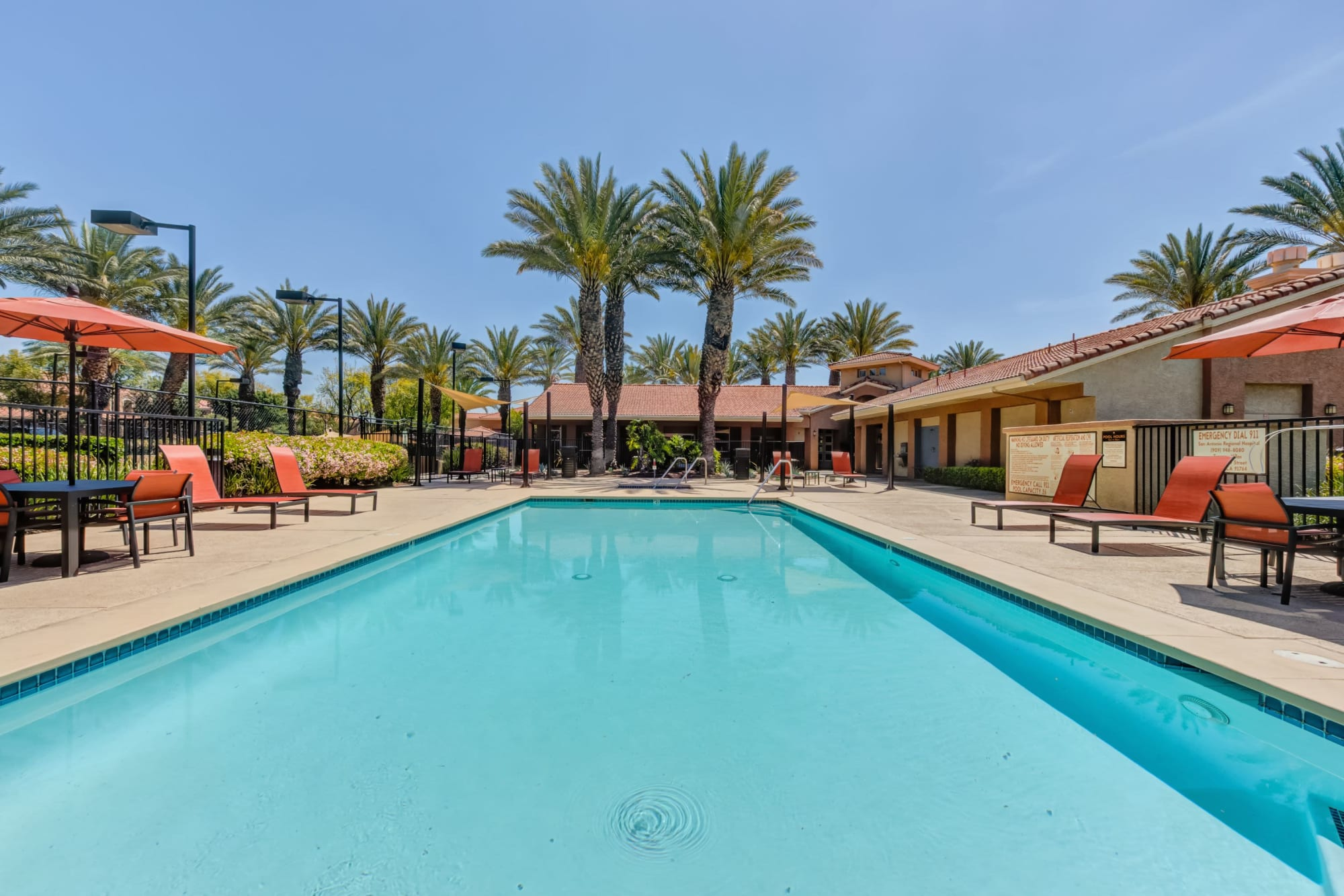 Pool view with umbrellas, lounge chairs and spa At Tuscany Village Apartments