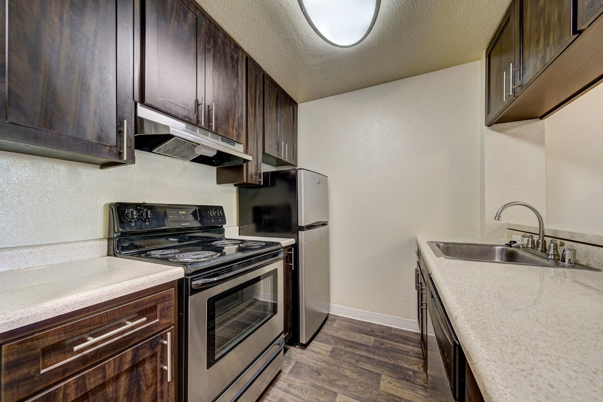 The Timbers Apartments offers a fully equipped kitchen - view of renovated brown kitchen with stainless steel appliances in Hayward, CA