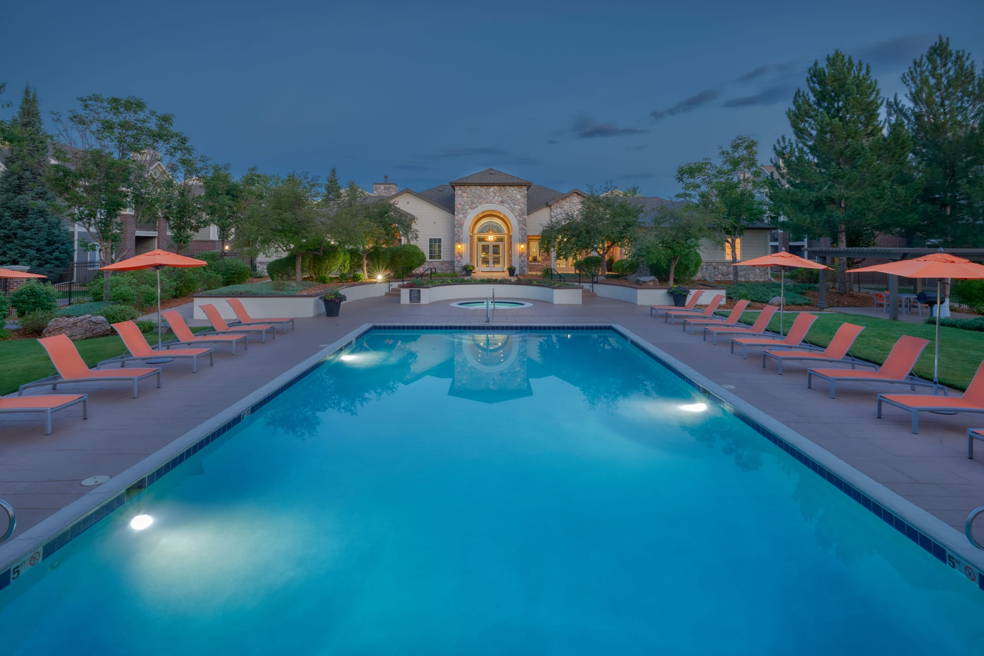 Pool area with lounge chairs at dusk at Legend Oaks Apartments in Aurora, Colorado