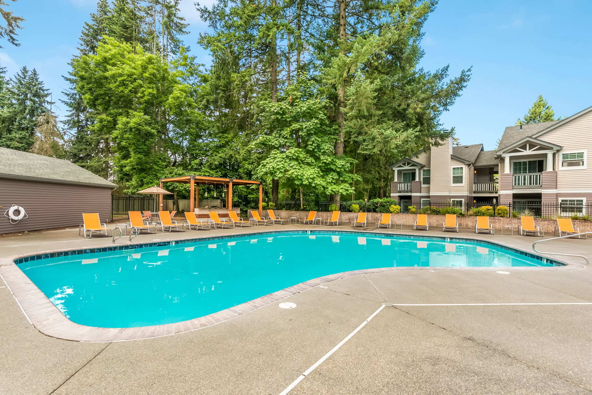 Bright blue pool with lots of seating and a covered barbecue area at Autumn Chase Apartments in Vancouver, Washington
