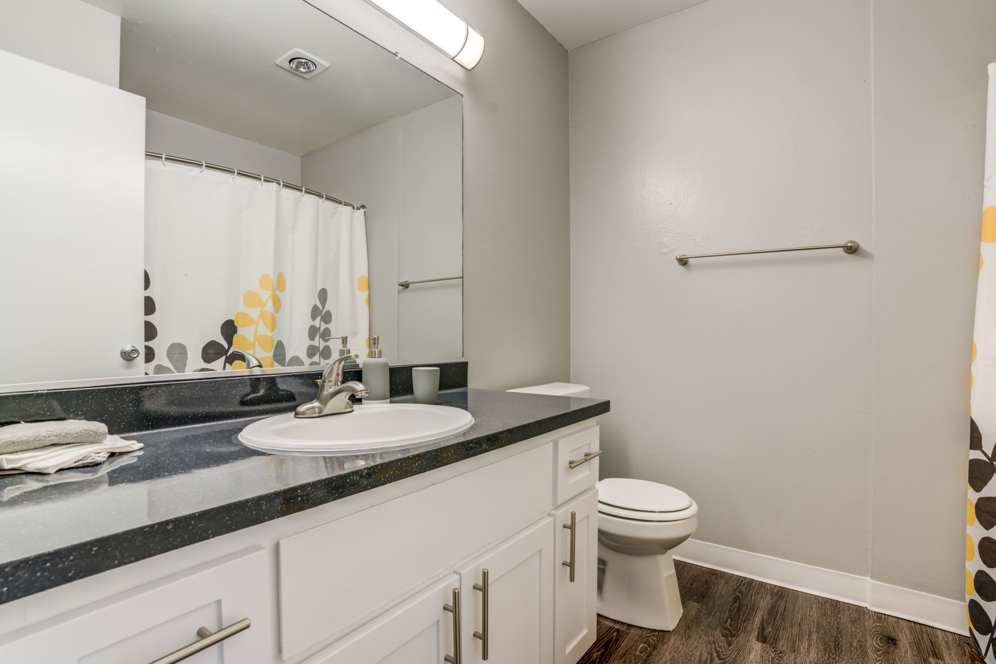 Renovated bathroom with white cabinetry at The Timbers Apartments in Hayward, California