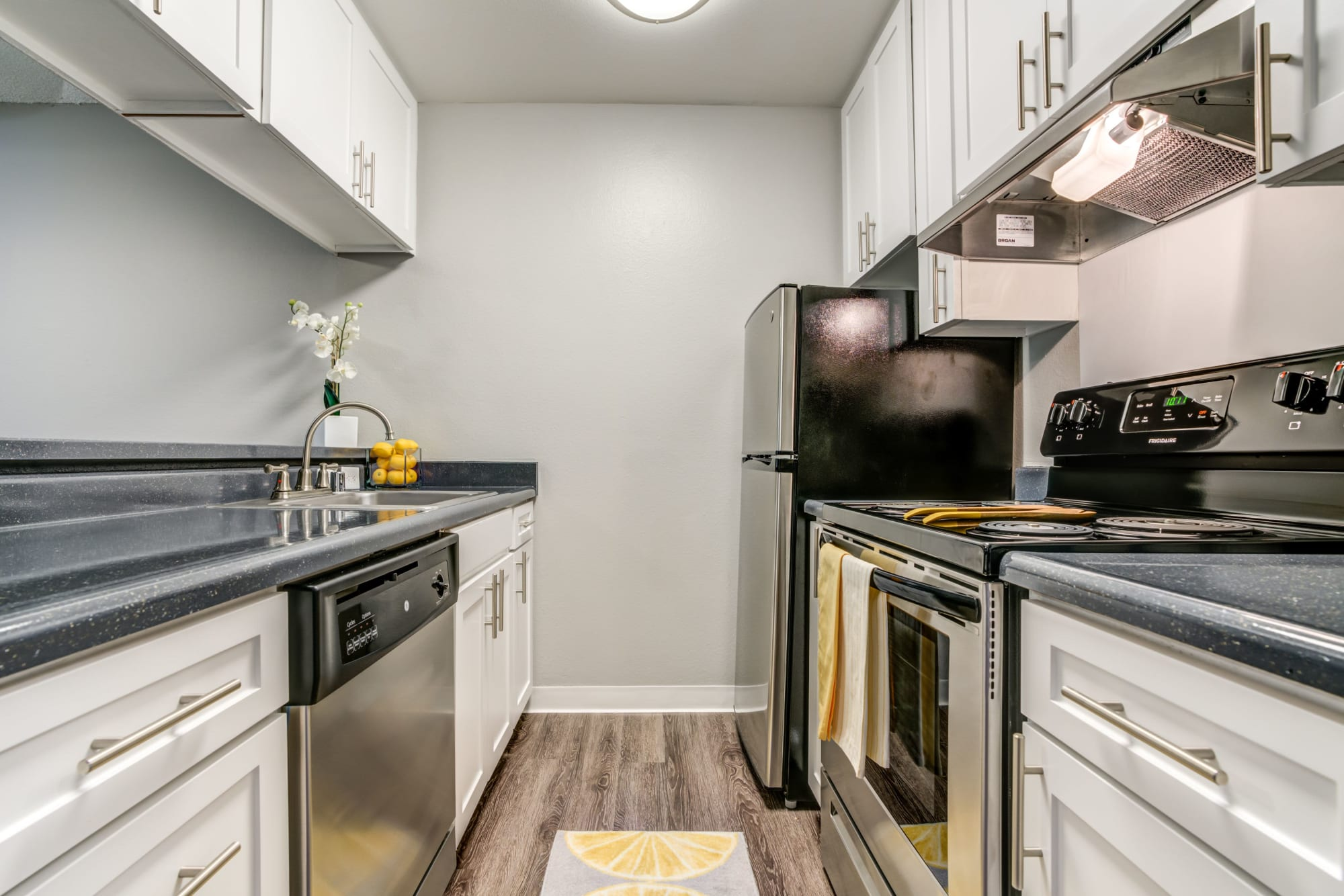 Renovated kitchen with white cabinets and stainless steel appliances at The Timbers Apartments in Hayward, California