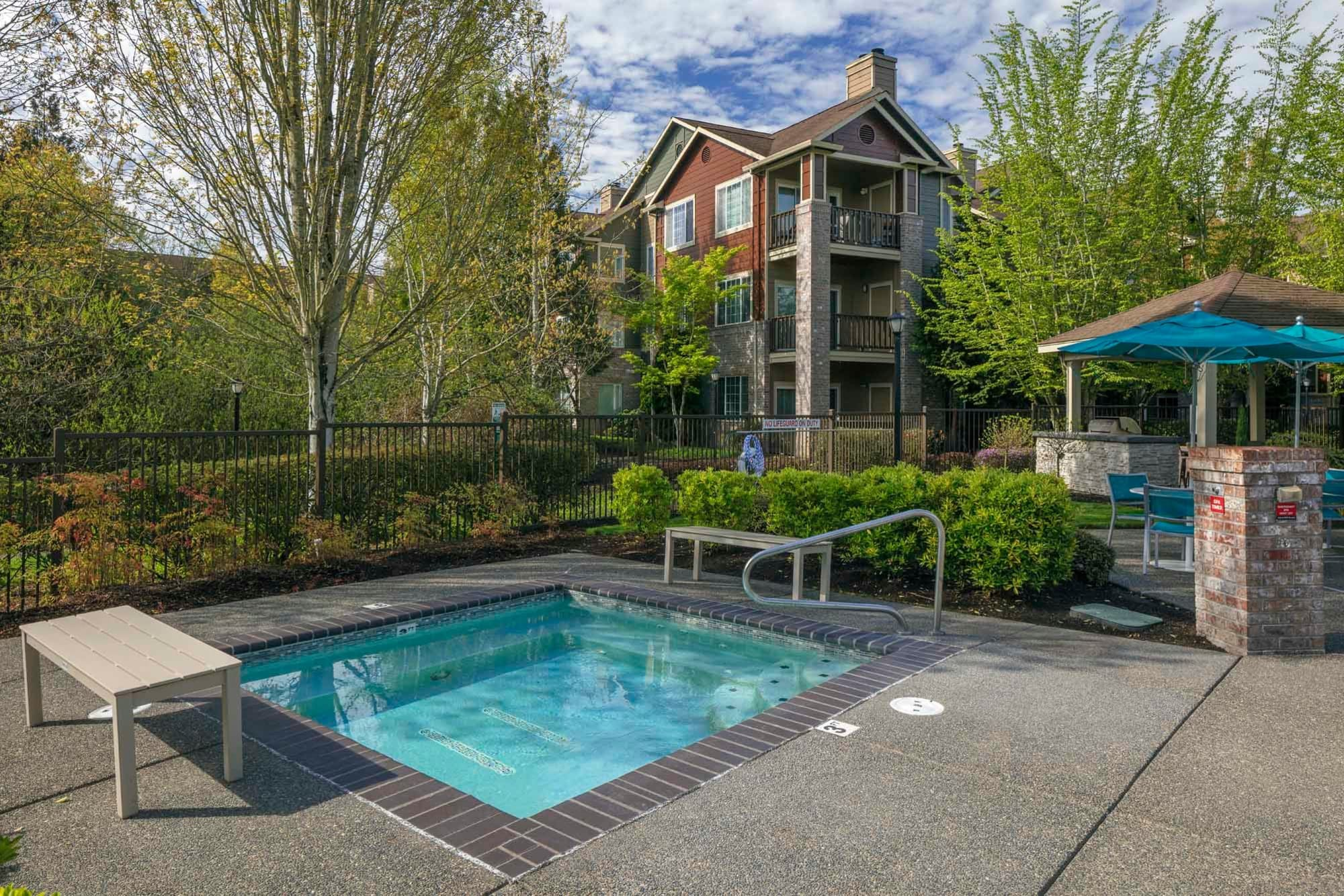 A hot tub with two benches next to it at The Grove at Orenco Station in Hillsboro, Oregon