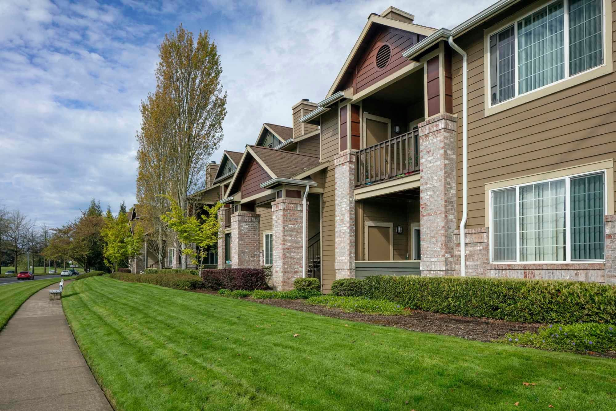 The side of the building with beautiful landscaping and lush green grass near The Grove at Orenco Station in Hillsboro, Oregon