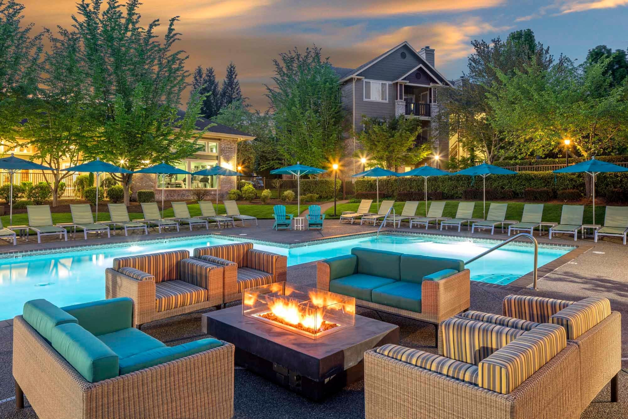 A fire pit surrounded by large chairs, poolside at The Grove at Orenco Station in Hillsboro, Oregon