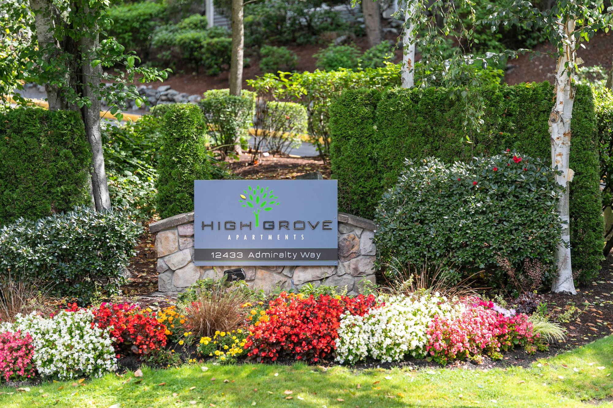 The monument sign surrounded by flowers at HighGrove Apartments in Everett, Washington